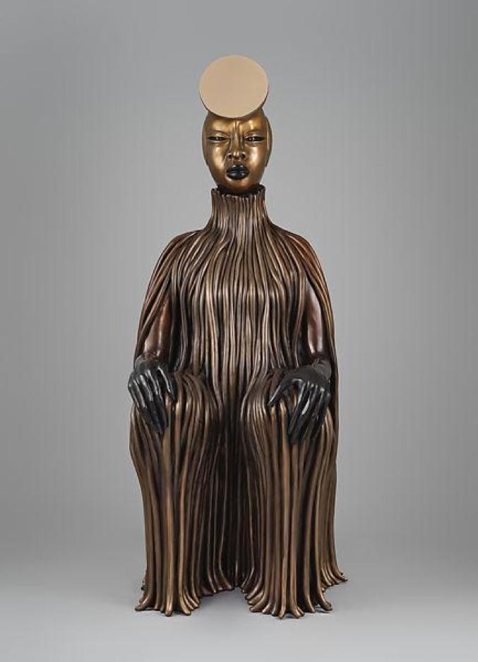 A bronze sculpture of a sitting figure