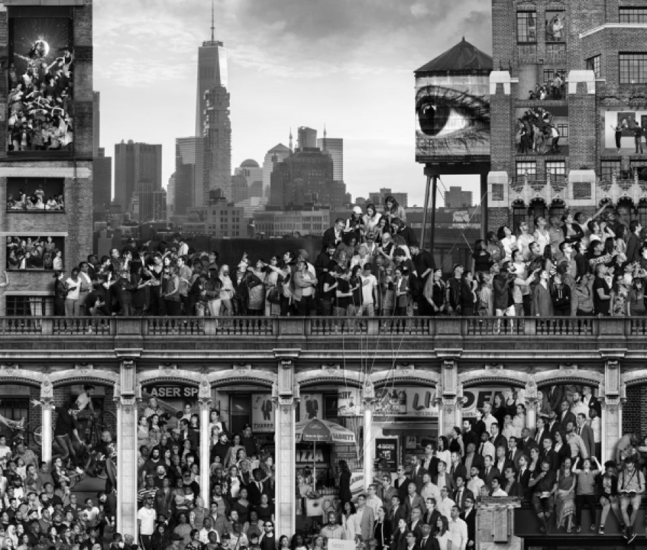 A black and white image of many people standing on and around an overpass.