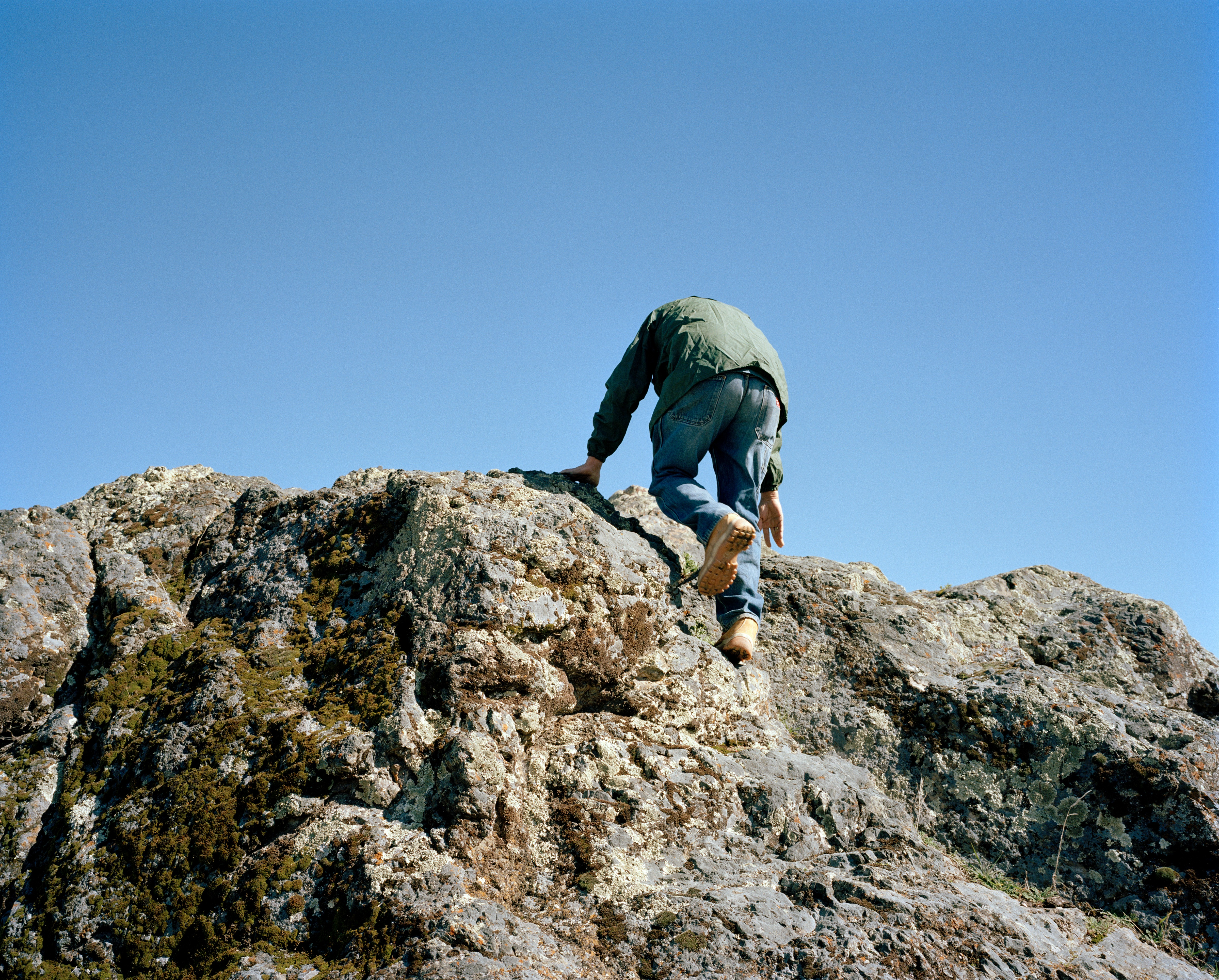 A photograph of a man climbing a rocky hill. The viewpoint is from behind and the sky is clear and blue.