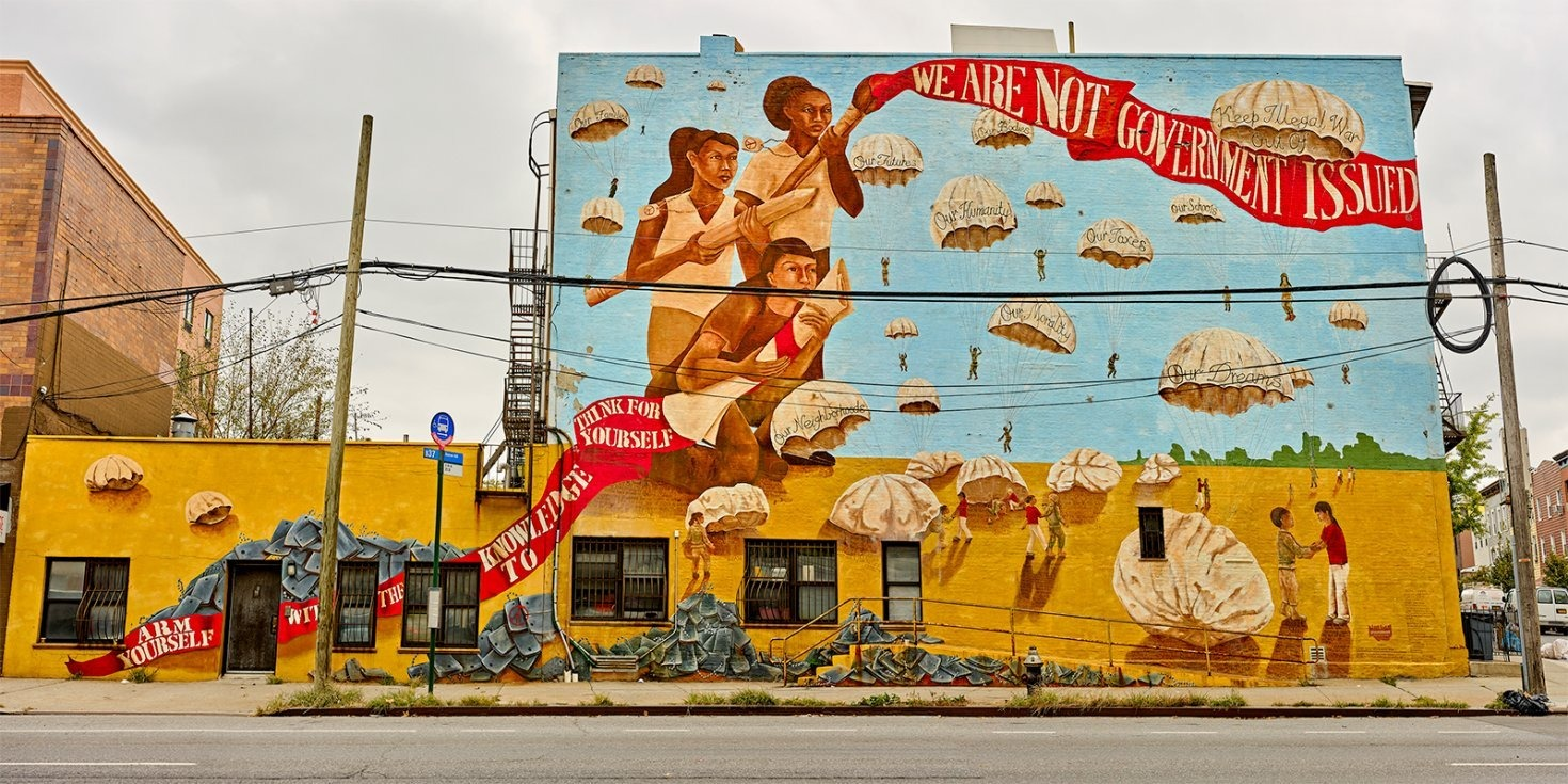 """Photograph of mural on side of building with three people holding a paintbrush, pencil, and paper respectively, with the text """"Knowledge to think for yourself / We are not government issued"""" superimposed on the red ribbon spreading throughout."""