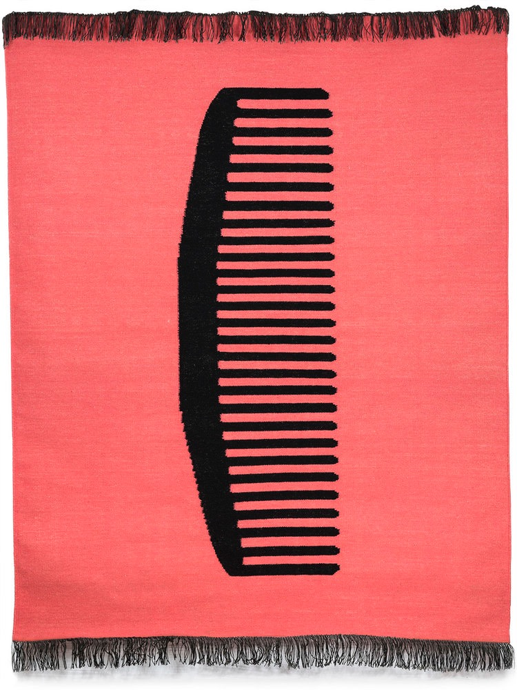 A photograph of a pink rug with a black-comb design stitched into it.