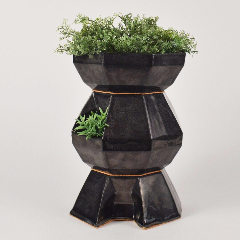 A photograph of a black-glazed ceramic compost pot that doubles as a planter.