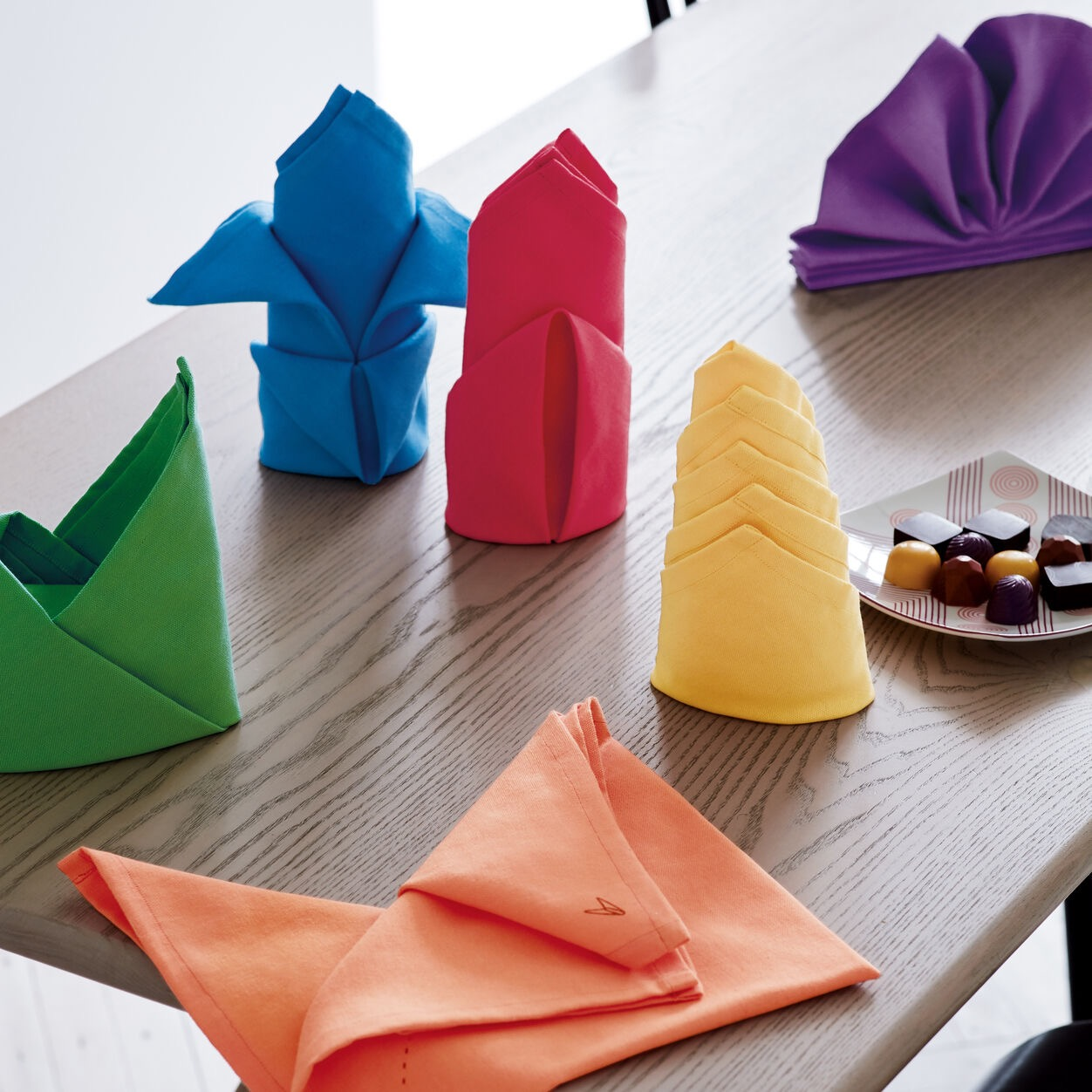 A photograph of folded napkins of different colors.