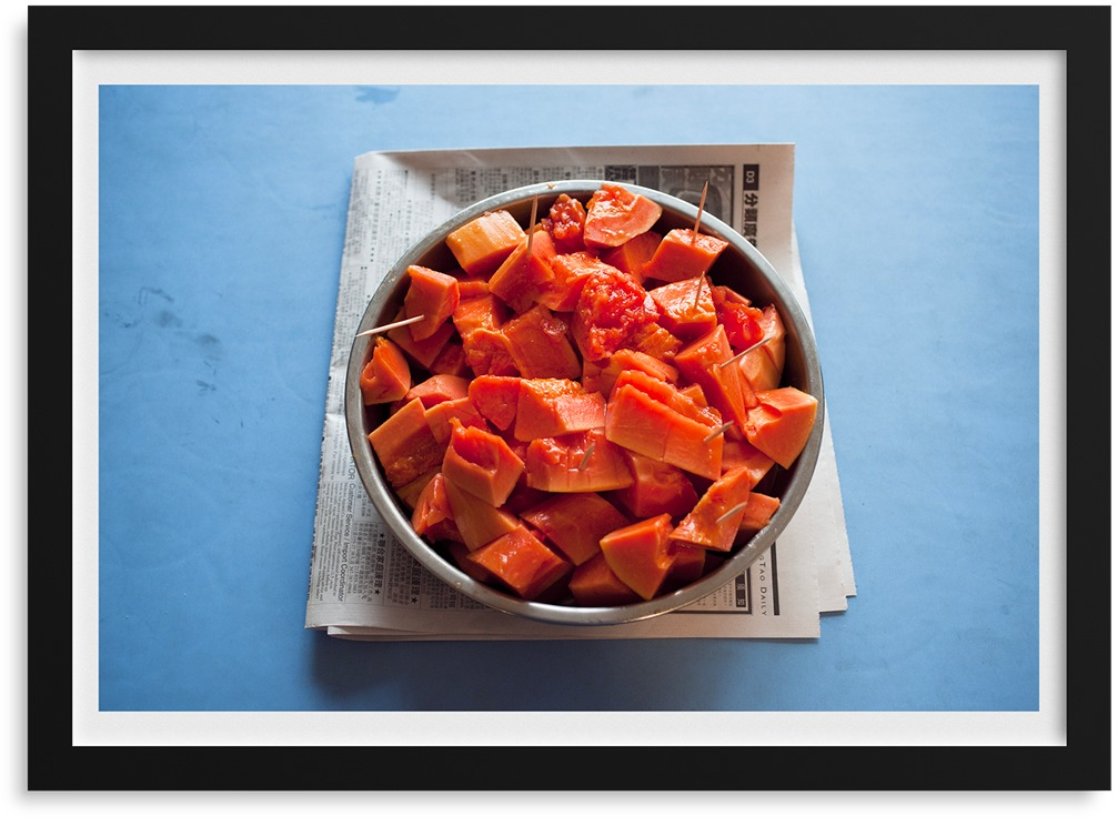 A color photograph of cut-up papaya in a metal bowl that is set on folded-up newspaper.