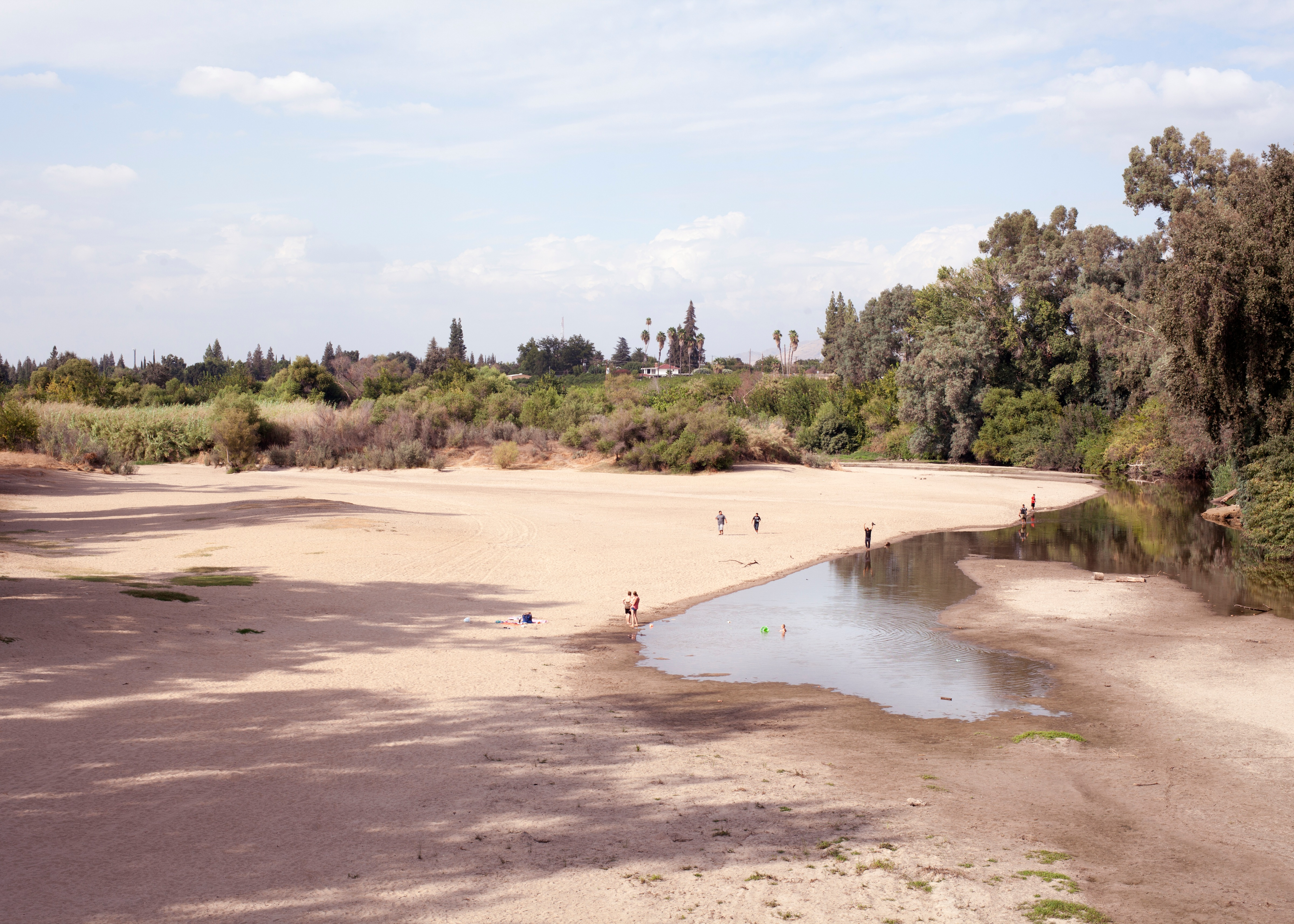 A photograph of a nearly dried riverbed, with several people standing at various spots along its edge.