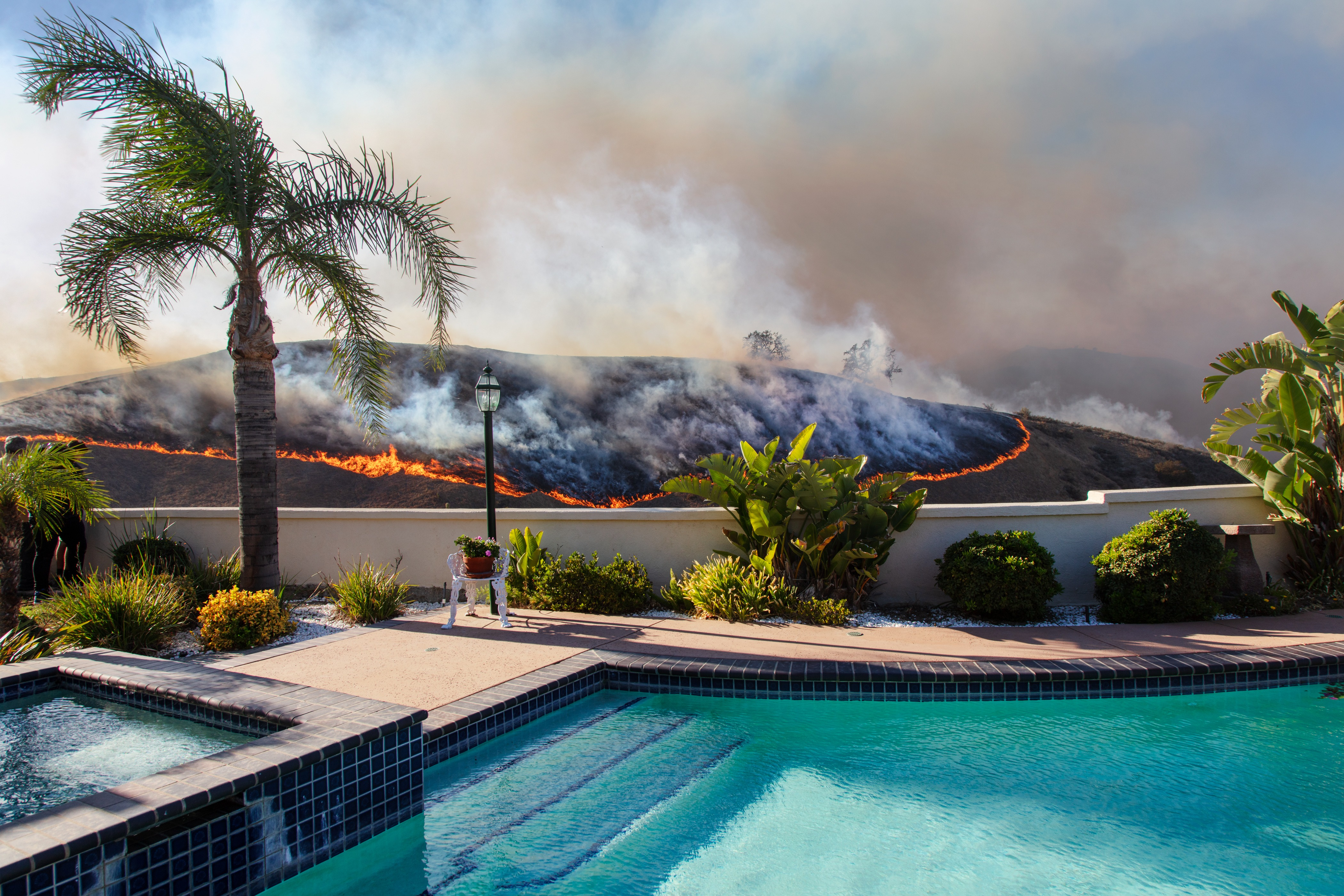 A photograph of a well-kept in-ground swimming pool and landscaped patio, with a wildfire burning on the hill just beyond its wall.