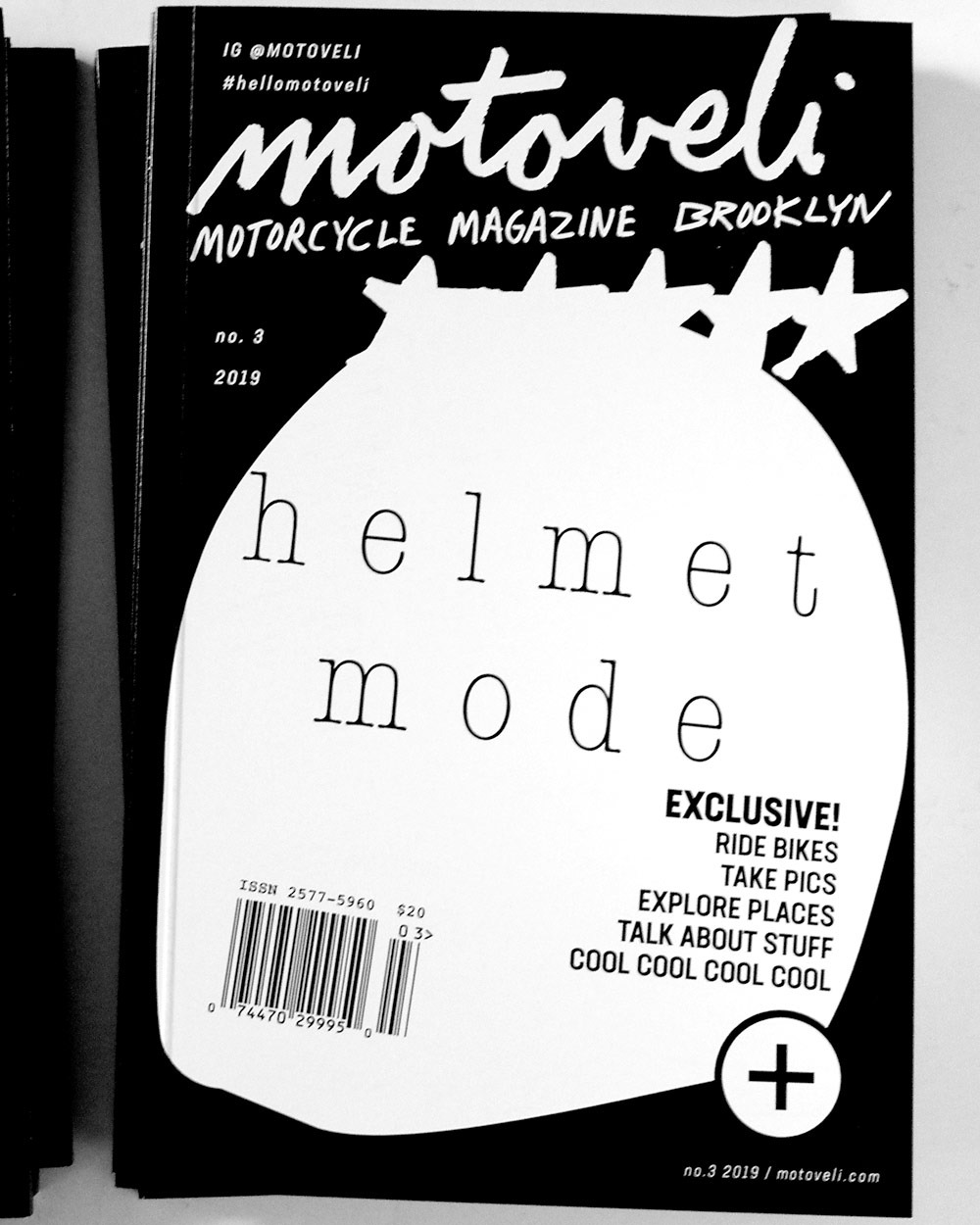 A black-and-white magazine cover featuring a white silhouette of a motorcycle helmet.