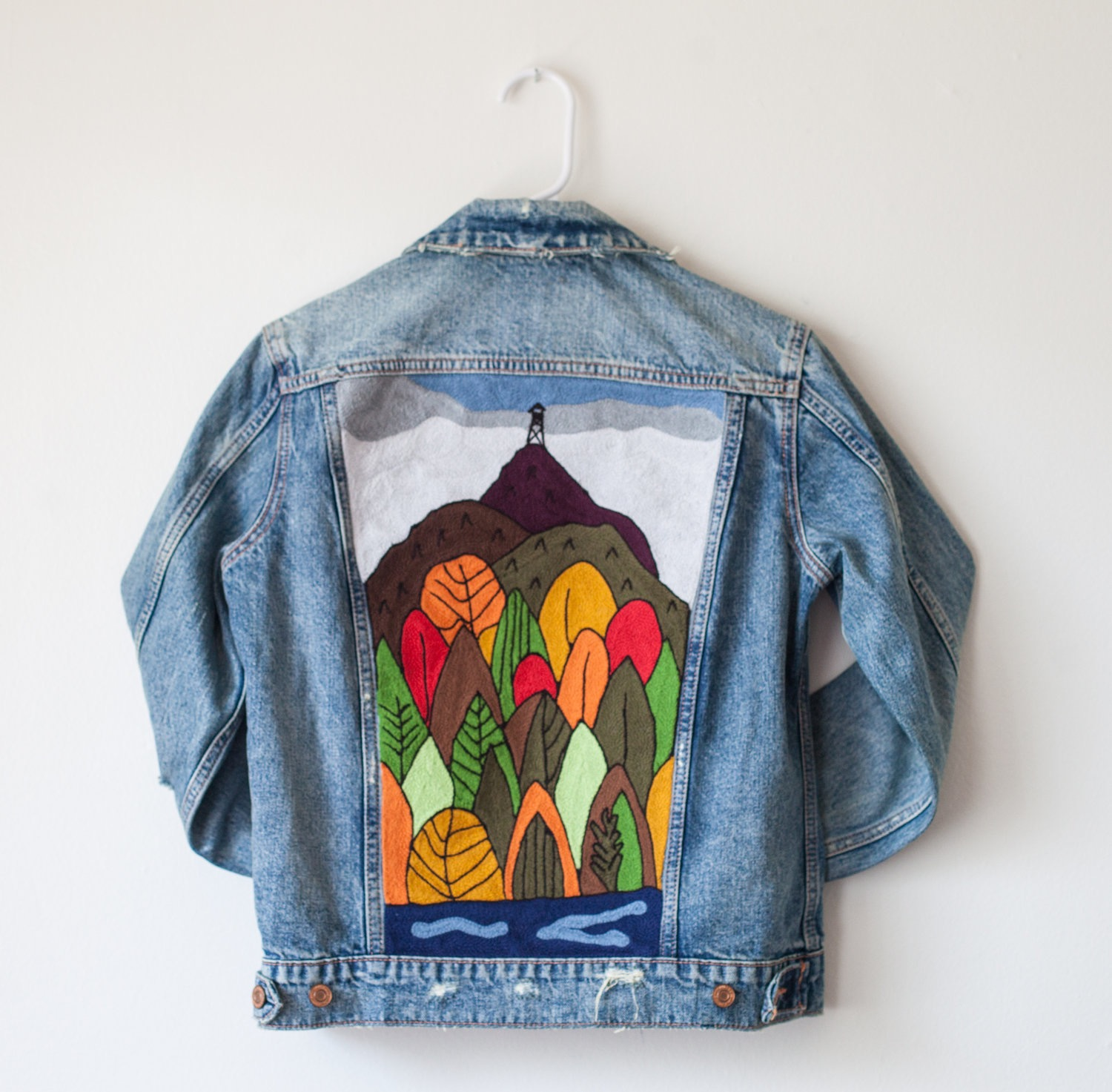 A photograph of a jean jacket with an embroidered image of a forest on the back.