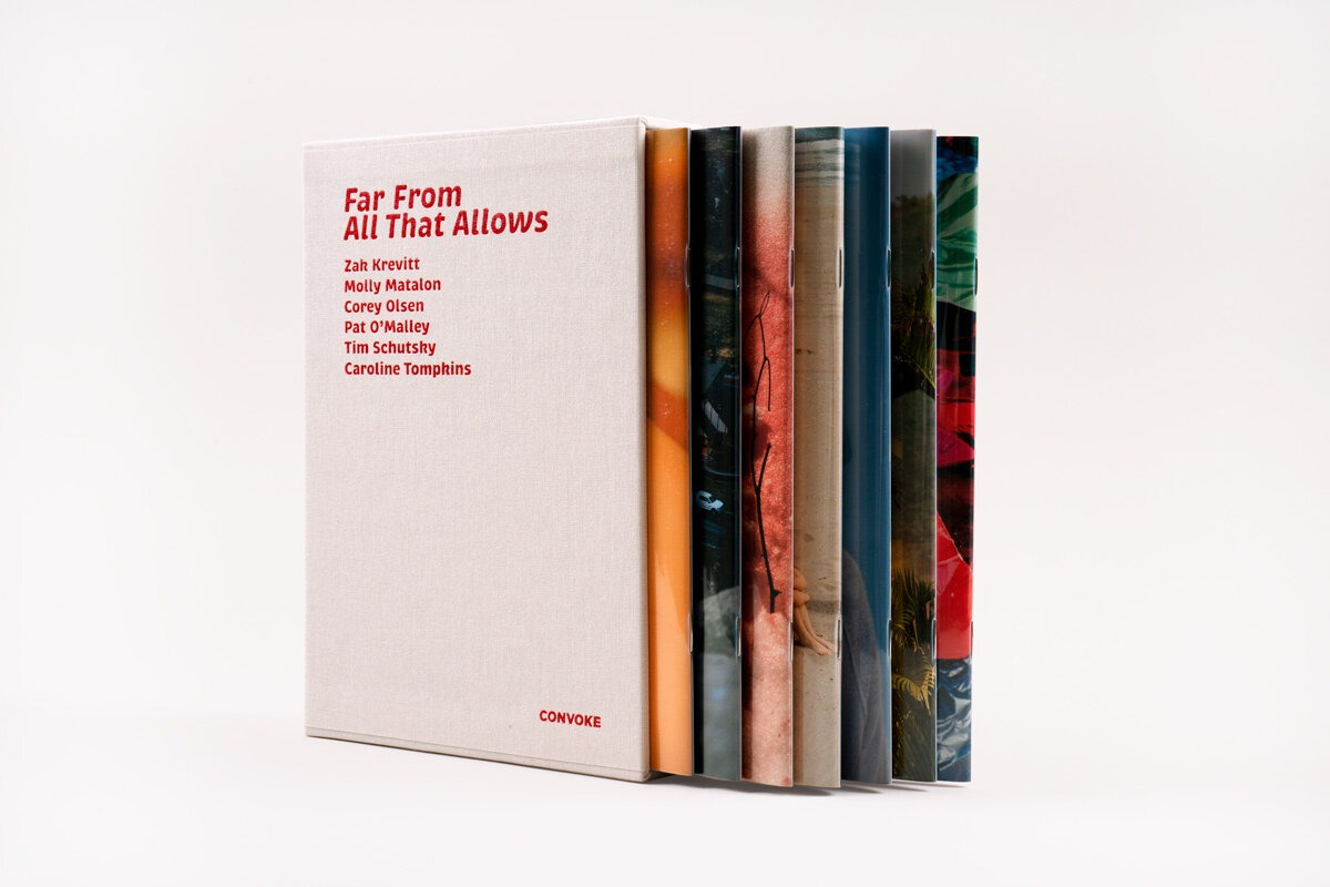 A photograph of a collection of slim books in a pale-colored slipcase.