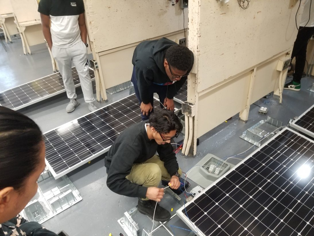 High school students crouch toward the ground in order to plug cords into hardware for solar panels, which surround the students in a workshop.