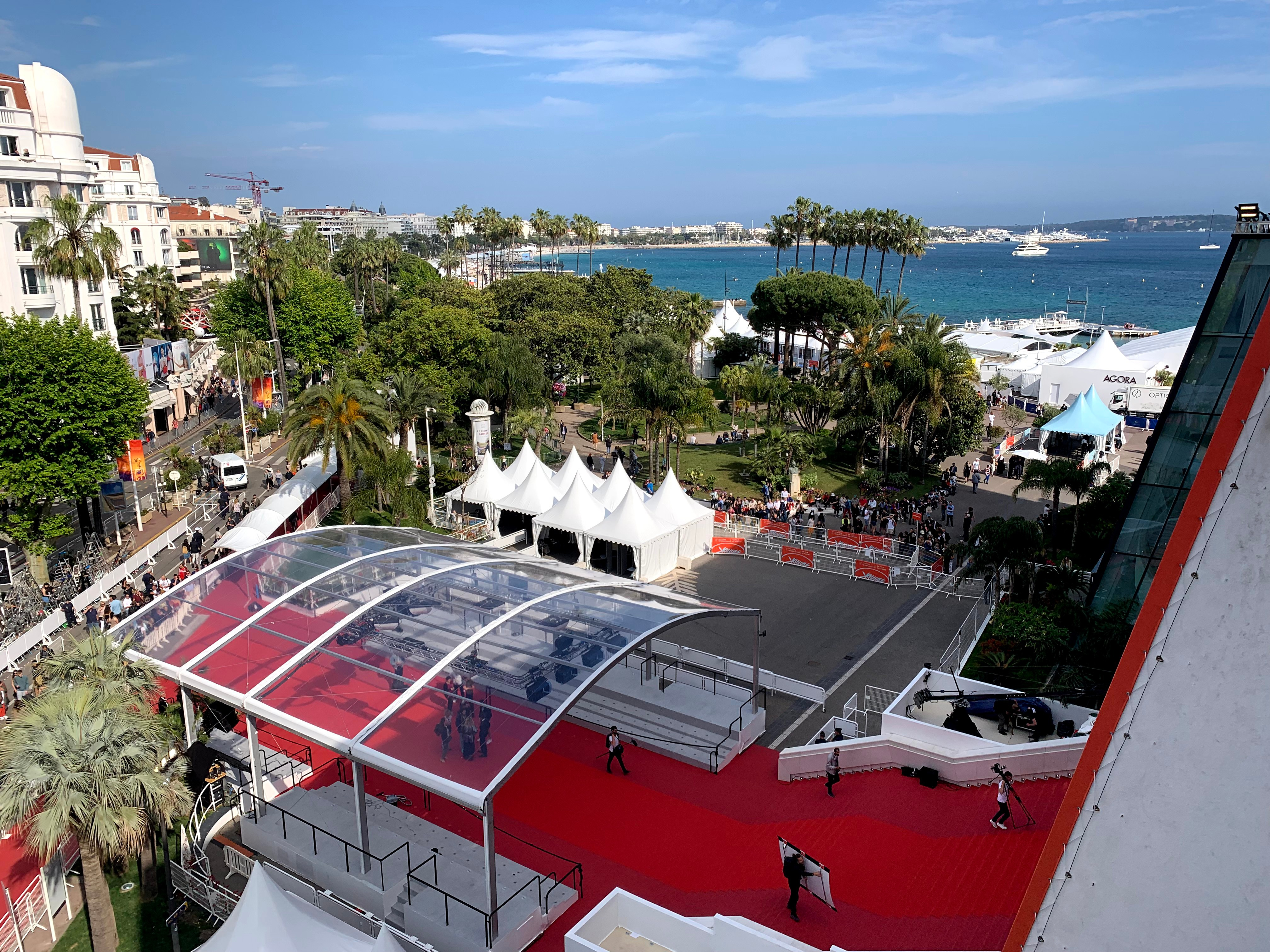 The Cannes Film Festival red carpet photographed from above, with a beach and palm trees in the background