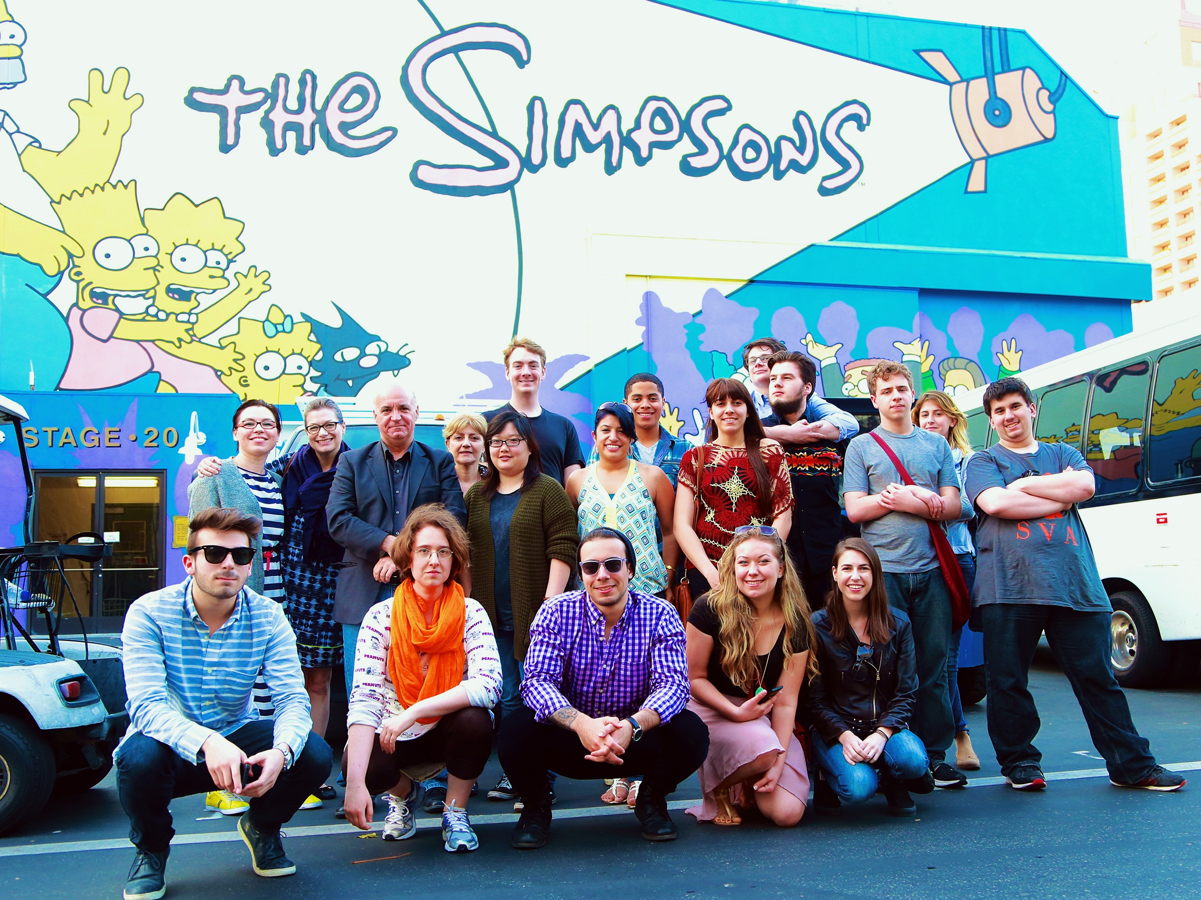 A group of people poses in front of The Simpsons lot in Los Angeles.
