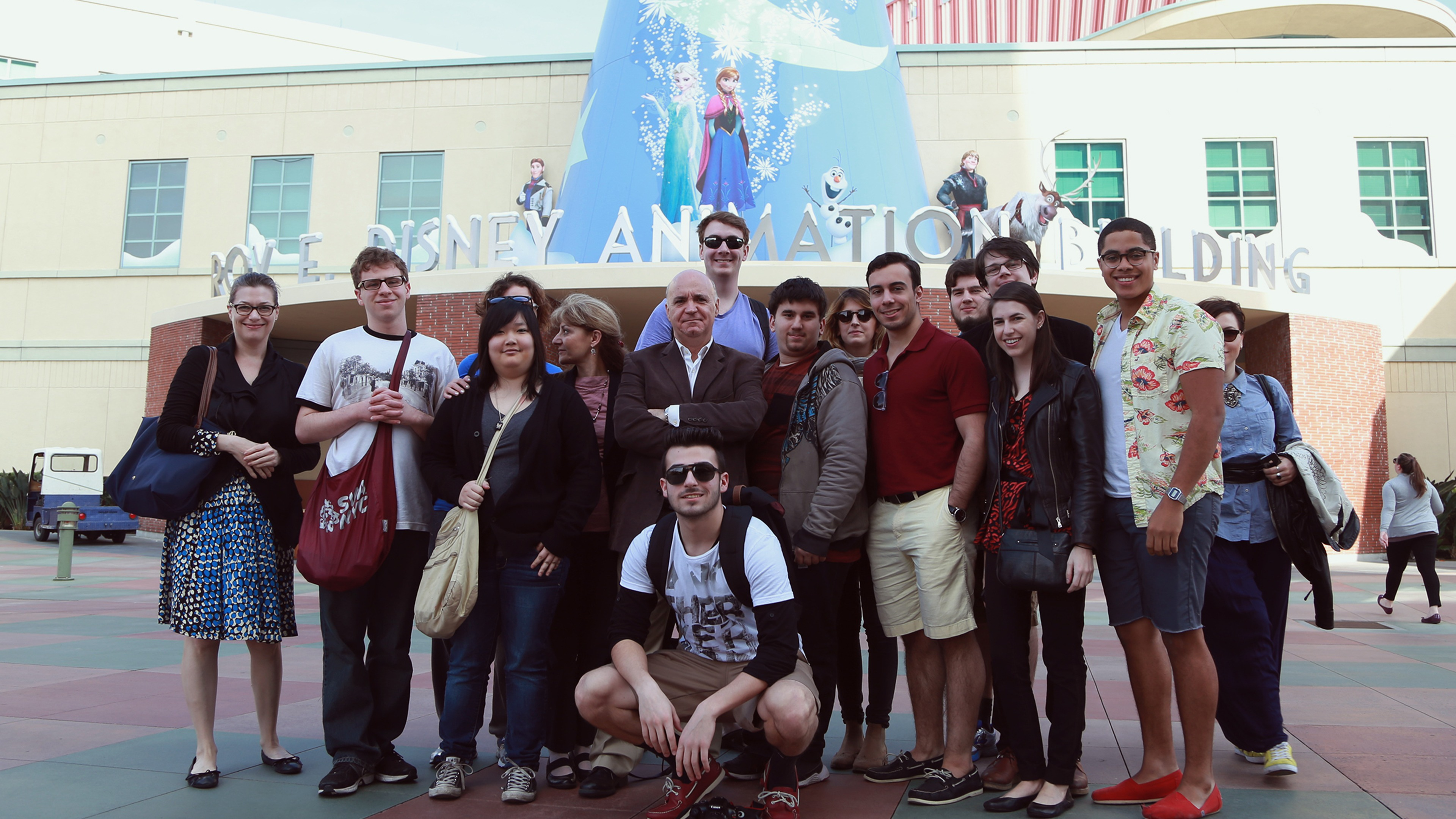 A group of students smiling outside of the Walt Disney Animation Studio entrance.