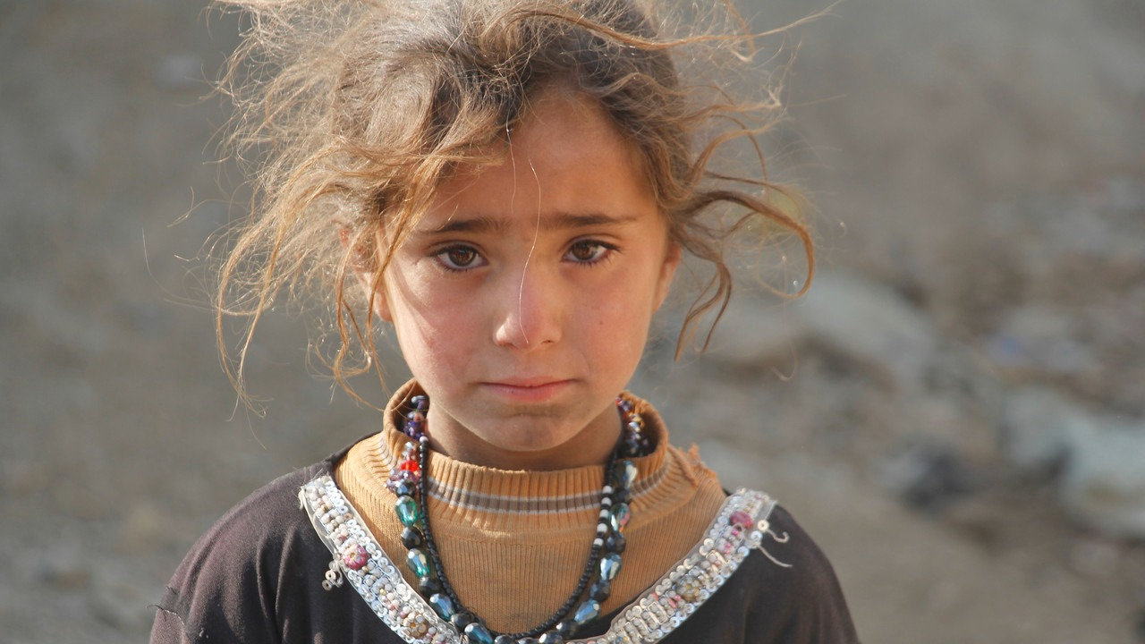 A medium portrait of a young Afghan girl with messy hair in partially torn clothing wearing a multi-colored beaded necklace who stares directly into the camera.