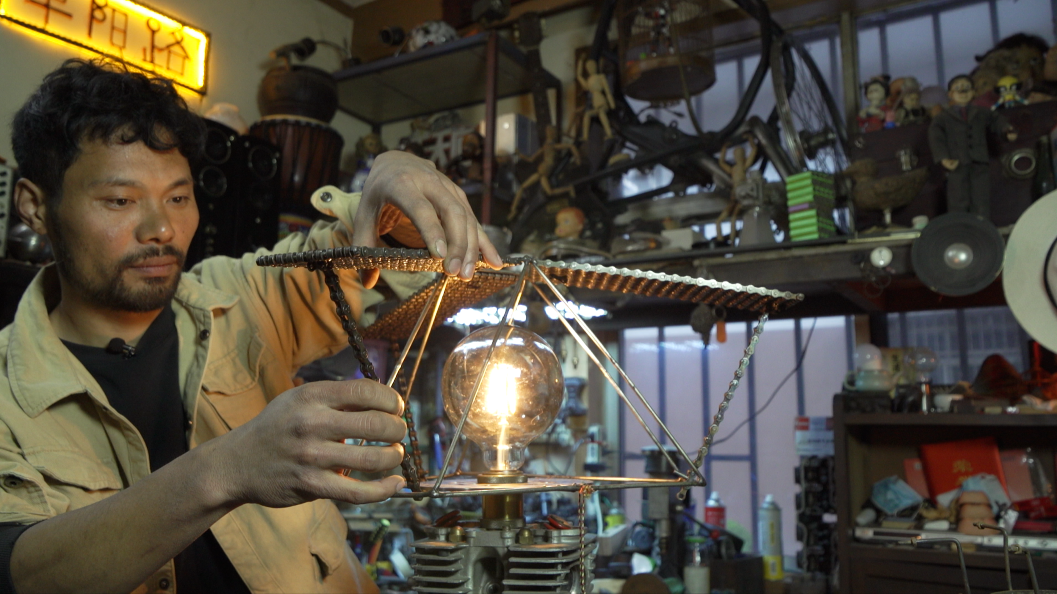 A man builds a sculptural lamp out of leftover motorbike parts in his cluttered studio.