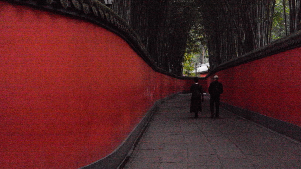 A long winding alley with red walls; in the distance, a couple walks through the pathway.