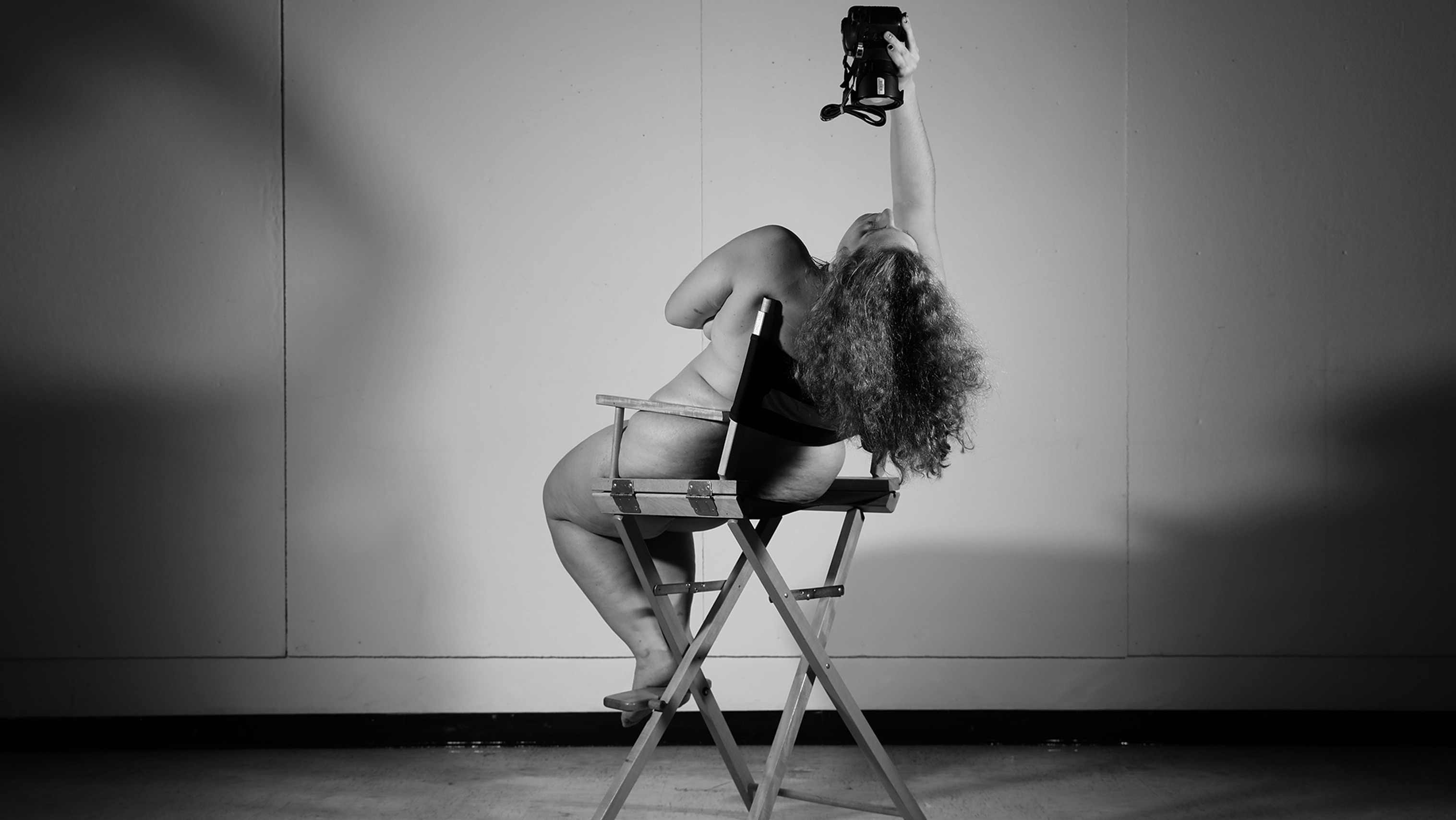 woman sitting nude on a directors chair taking a selfie with camera positioned above.