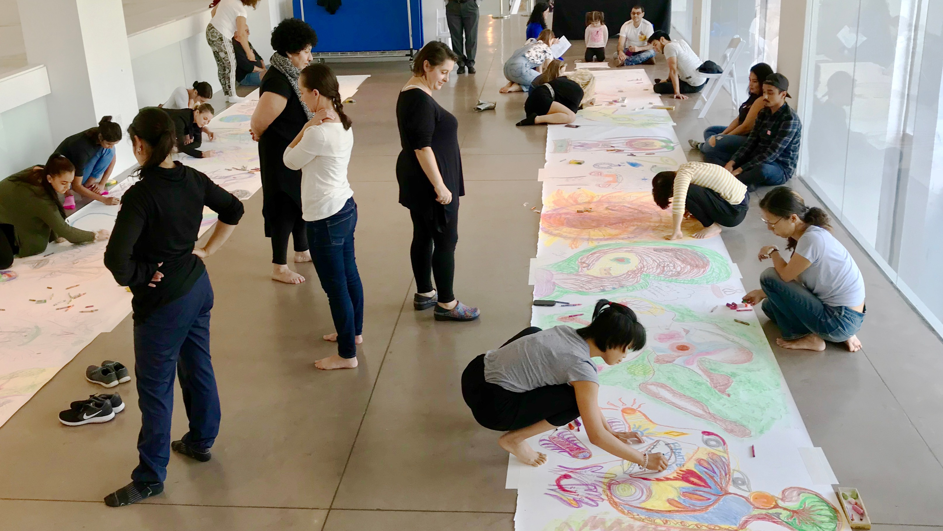 a room full of students drawing on a roll of paper on the floor.
