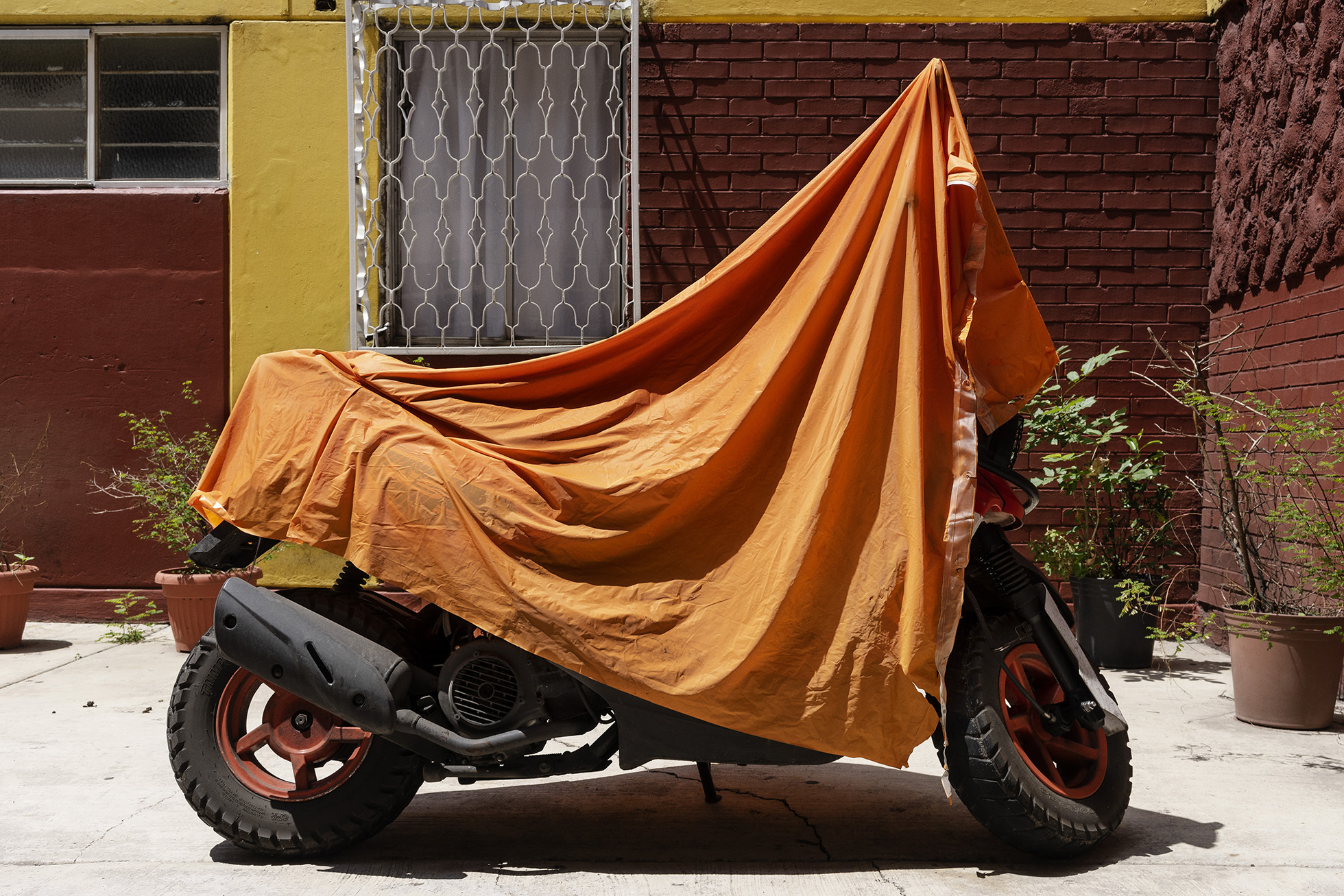"""<p """"="""""""">A color photograph of a parked motorcycle with an orange tarp thrown over it."""