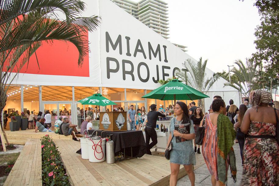 People attending an event. The wall says Miami Project.