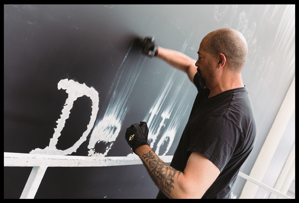 """<p """"="""""""">Artist Gary Simmons uses his fists to smudge the wet paint of white letters on a black wall."""