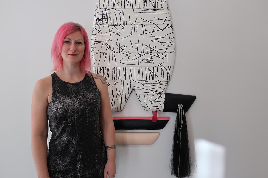 A woman with short pink hair in a black dress standing next to a sculture. The sculture is abstract, white with black lines. Under the sculpture is a tassle and a pink and black shelf.