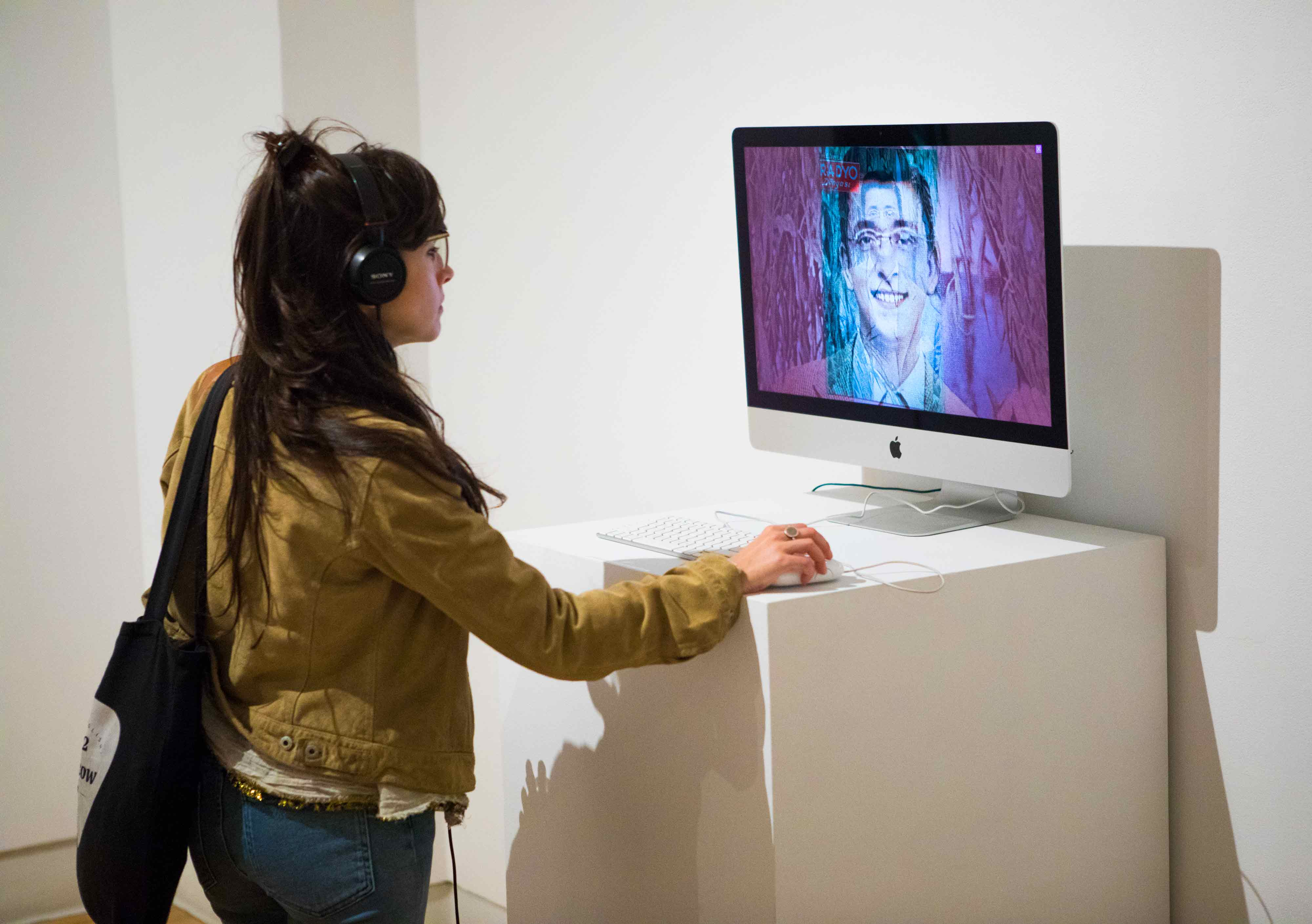 A young woman watching a video about another person.