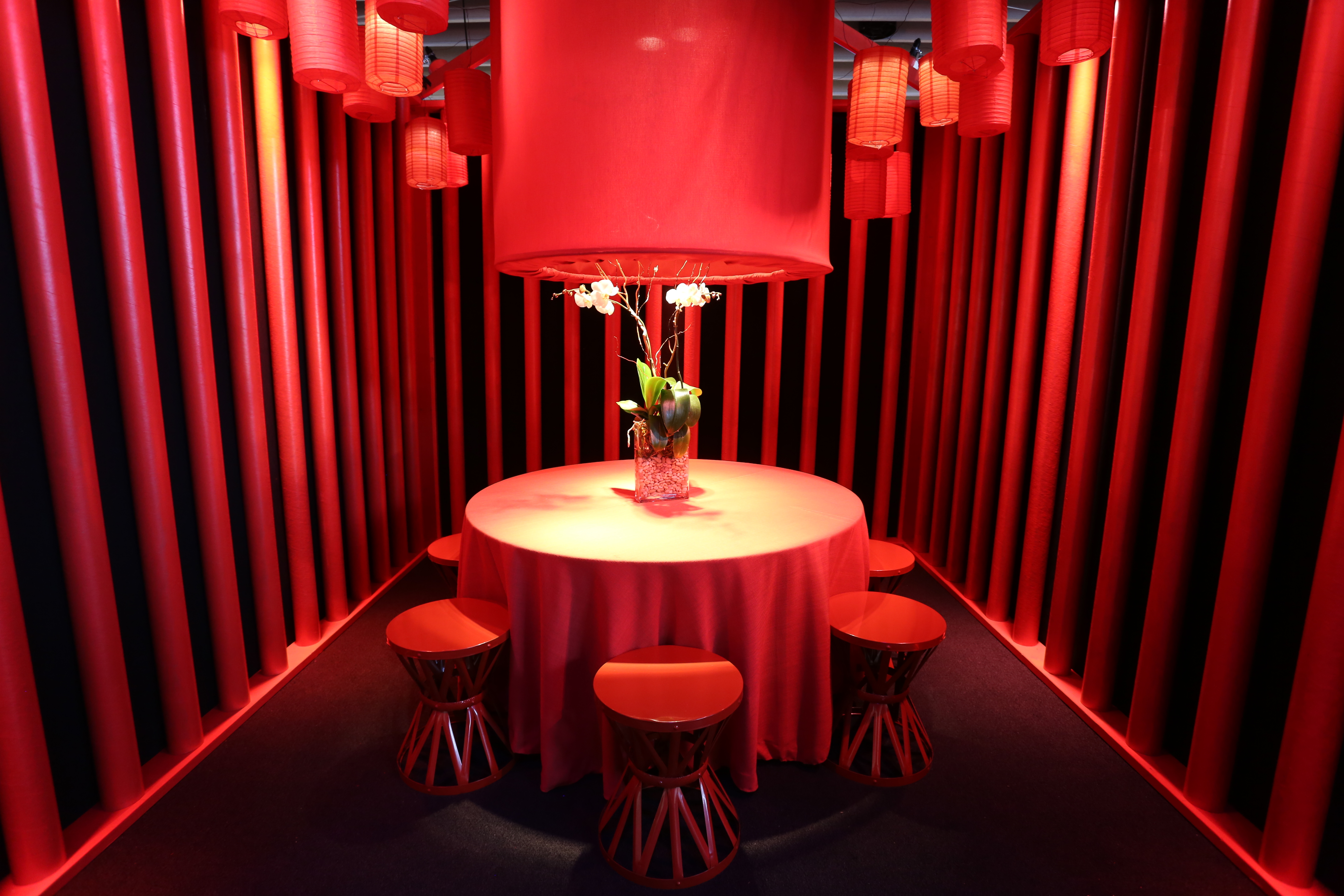Empty room with walls covered by red drapes. a round red table in the center of the room with a floral arrangement on top and red paper lanterns hanging above it.