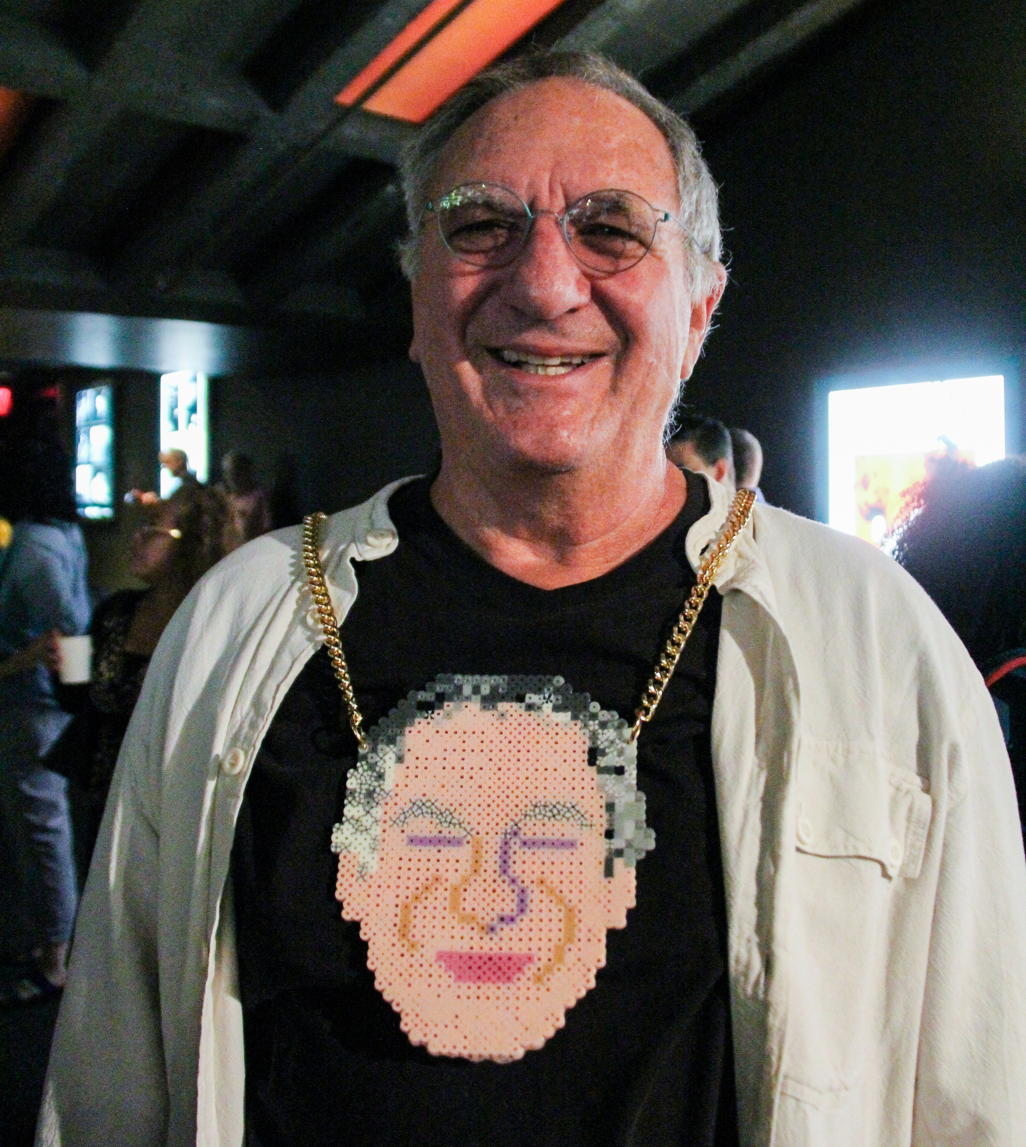 Richard Wilde smiles, wearing a chain with a pendant of his face made out of beads.