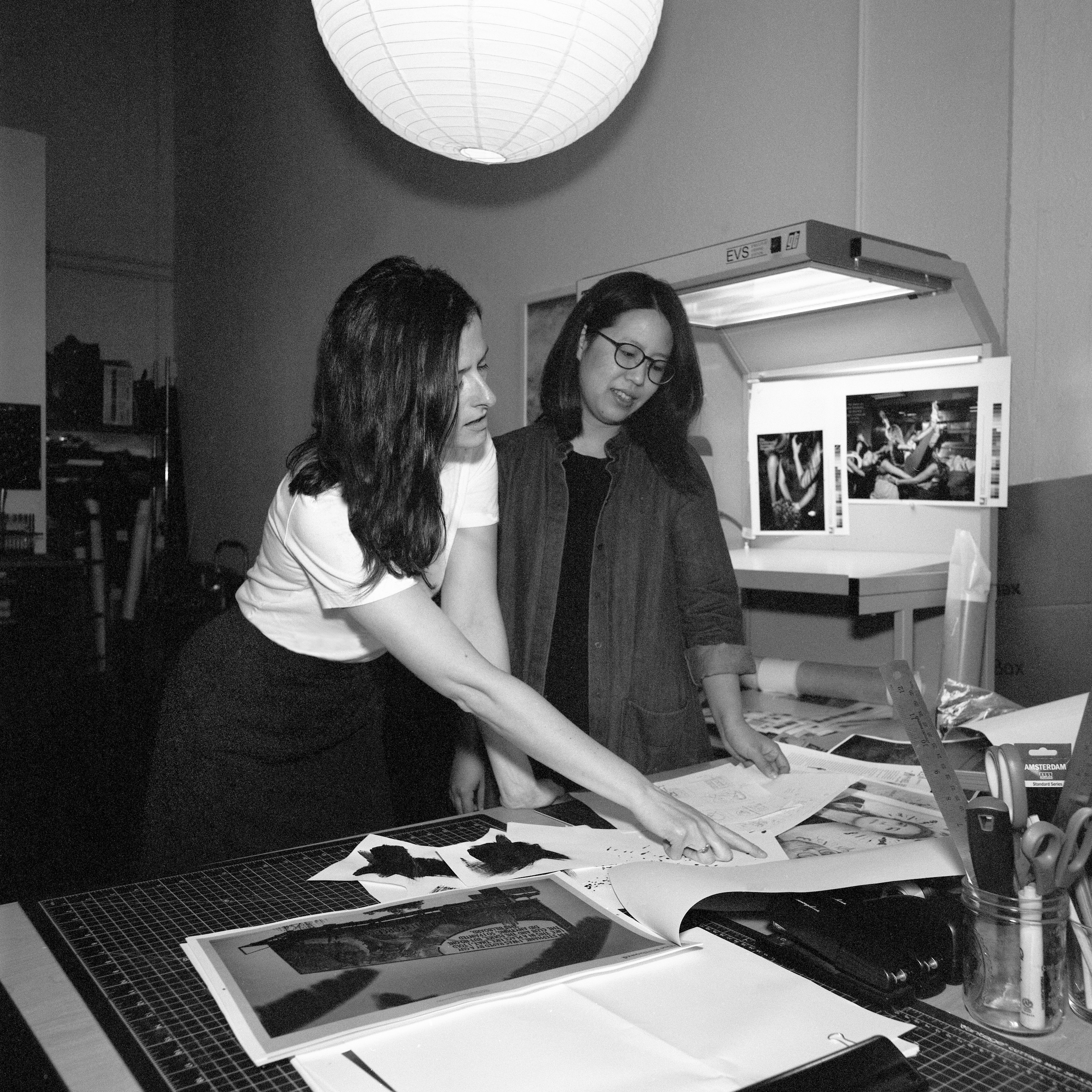 "<p ""="""">A black-and-white photograph of two women standing at a work table covered with printouts and photographs."