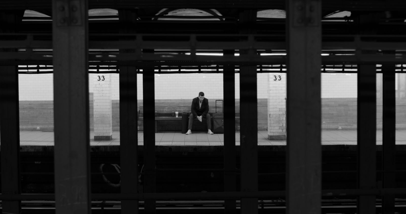 Man sitting waiting for a train in a subway