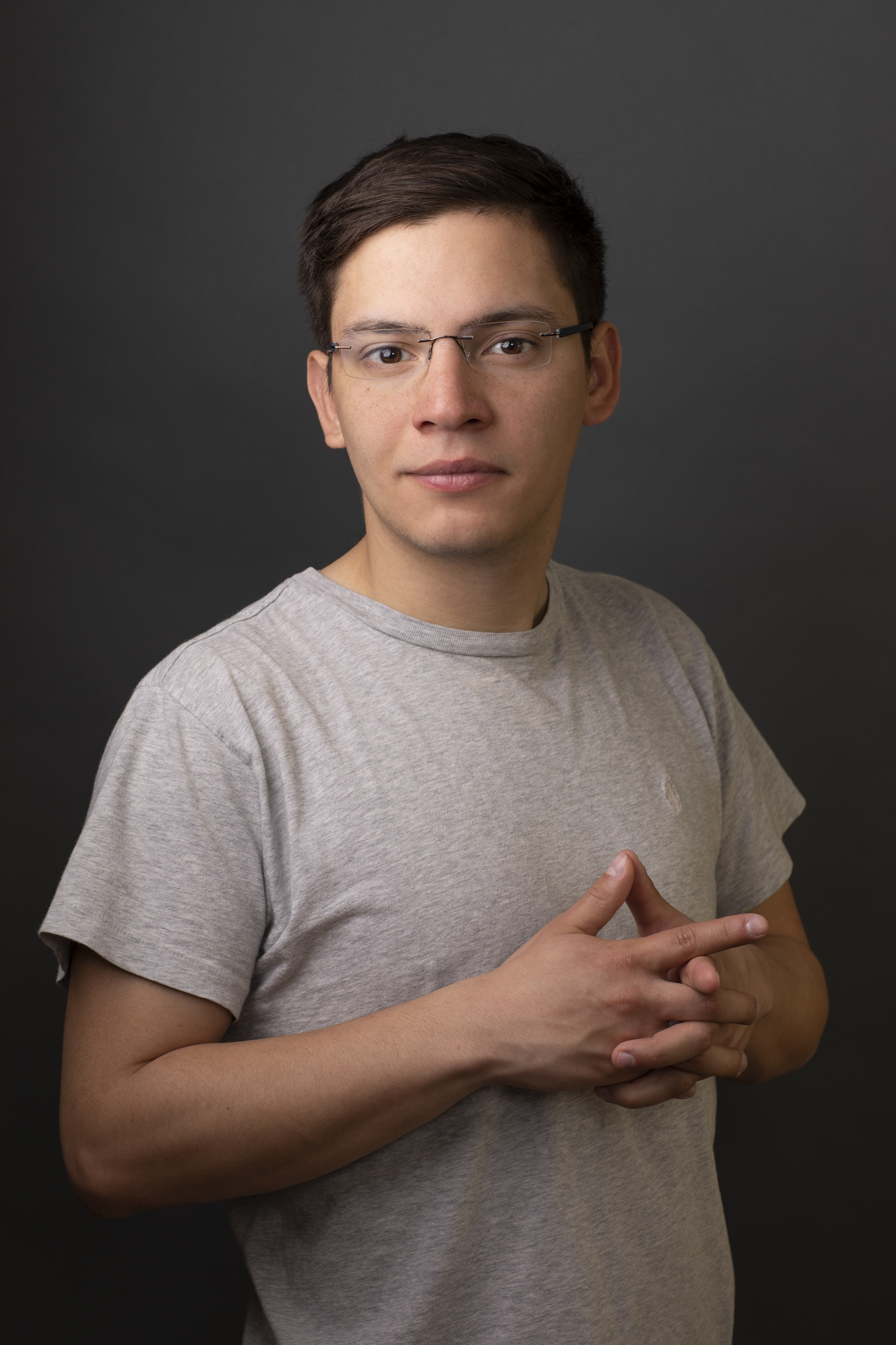 """<p """"="""""""">A color photograph of a young man standing in front of a monochrome backdrop, with his hands clasped at his chest."""