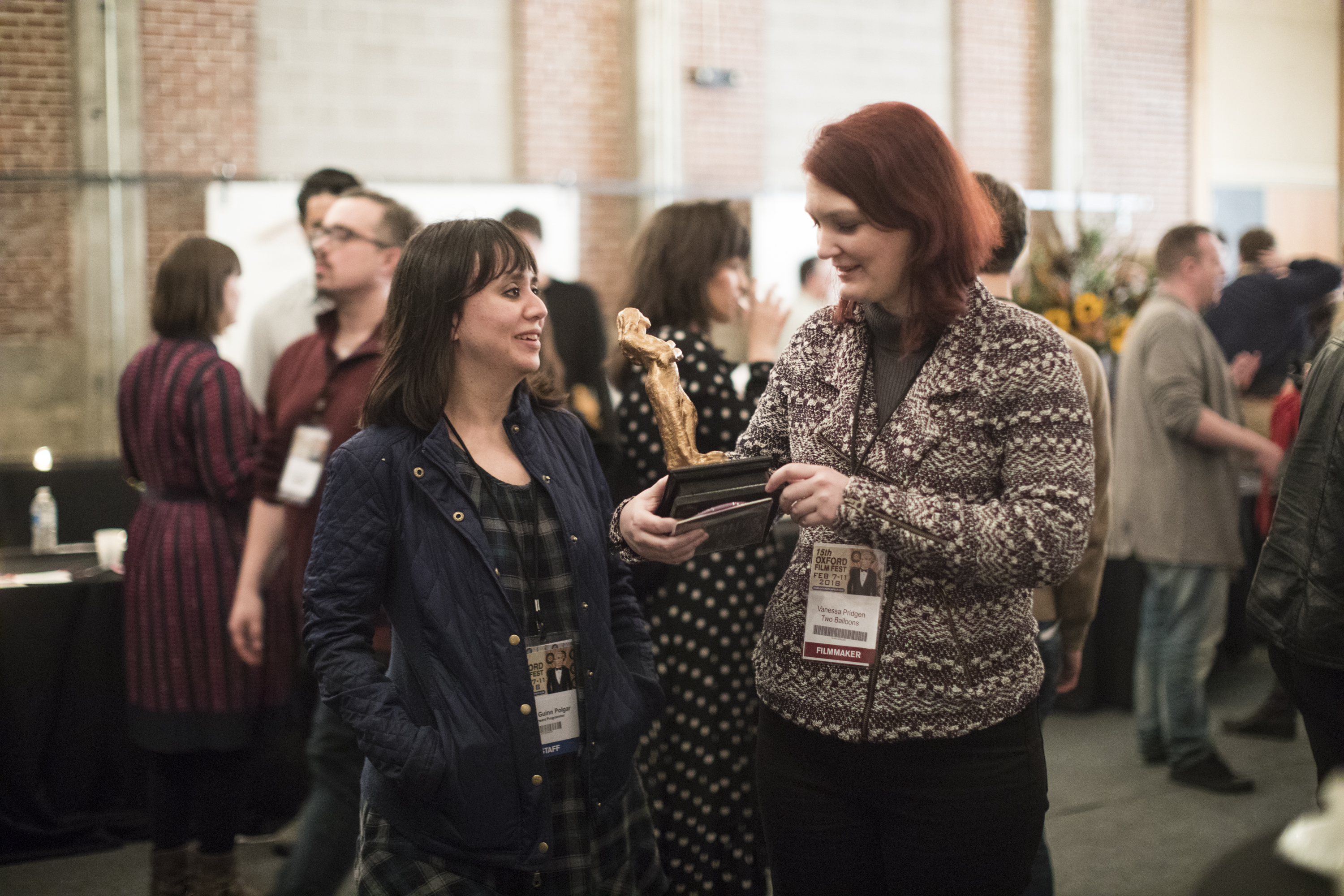 Two women talk at a crowded convention. The two women are friendly