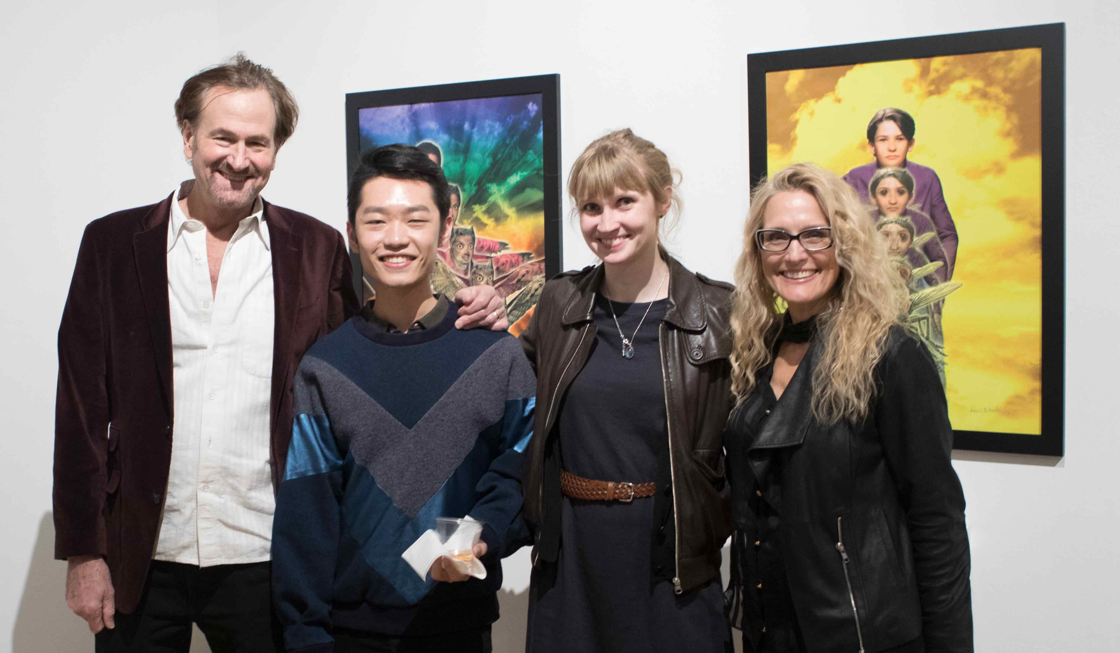 Four people standing together in front of a wall with two framed posters.