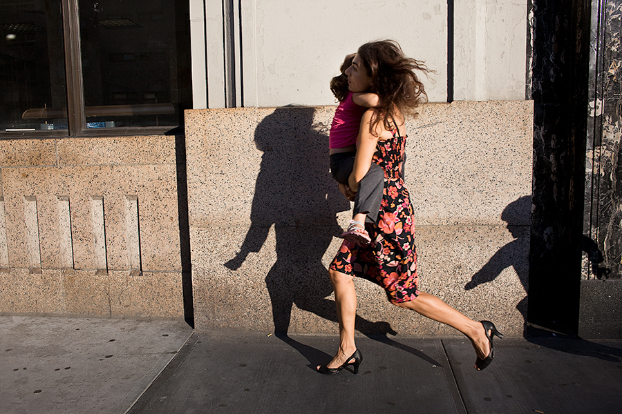 A woman holding a child and being chased down the street (as seen in the shadow). The woman is wearing a floral dress and black heels.
