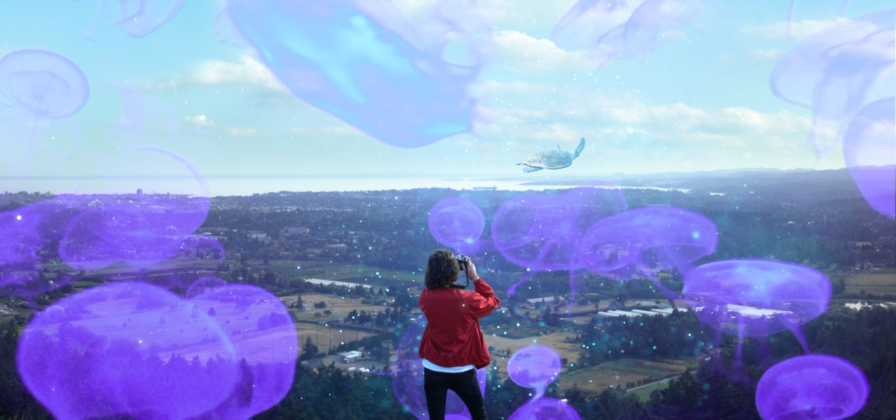 The back of a young woman holding a camera up, taking a photograph of the vast landscape in front of her. There is a flying turtle in the distance and bright purple translucent jellyfish in the sky all around her.