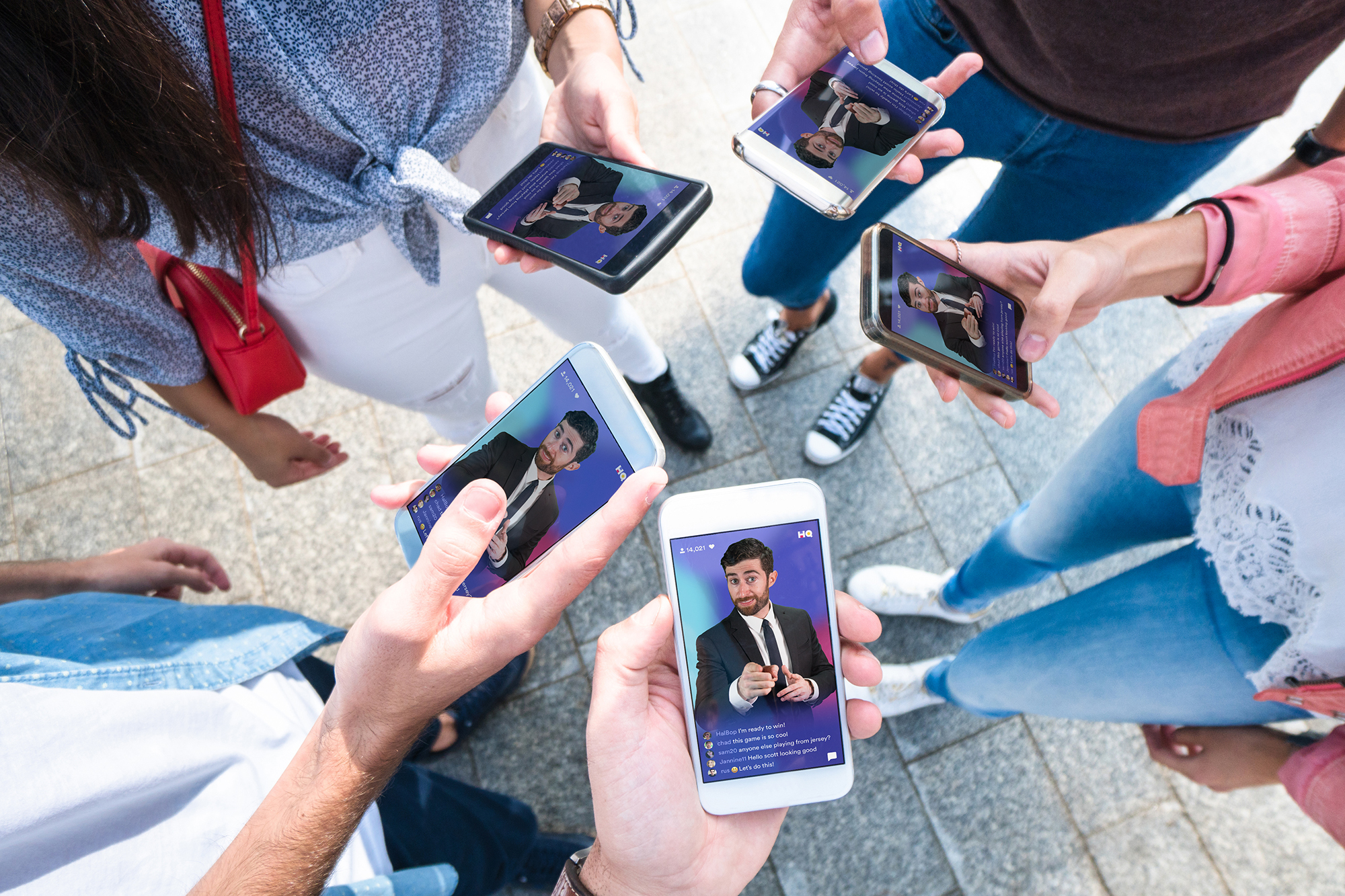 A group of people playing HQ Trivia on their phones.