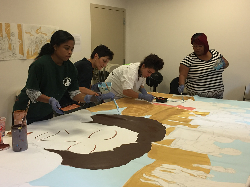 A group of students working together to paint a large mural. The mural has very little details of humans.