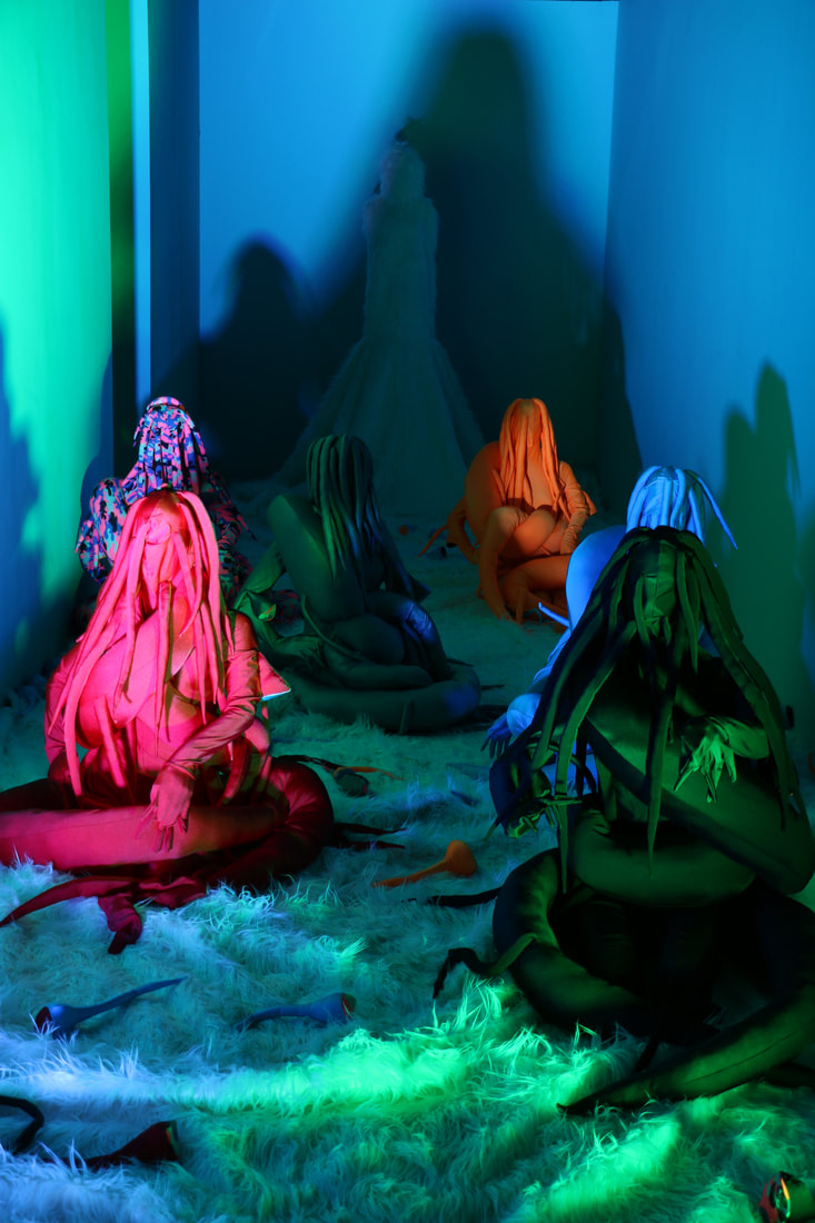 Five people sitting on the floor are dressed in different solid colors and one in checks.  The costumes are reminiscent of snakes with tail wrapping around their bodies.