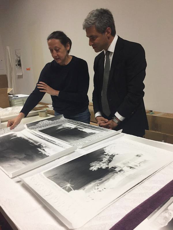 A man and woman discussing and looking at images.