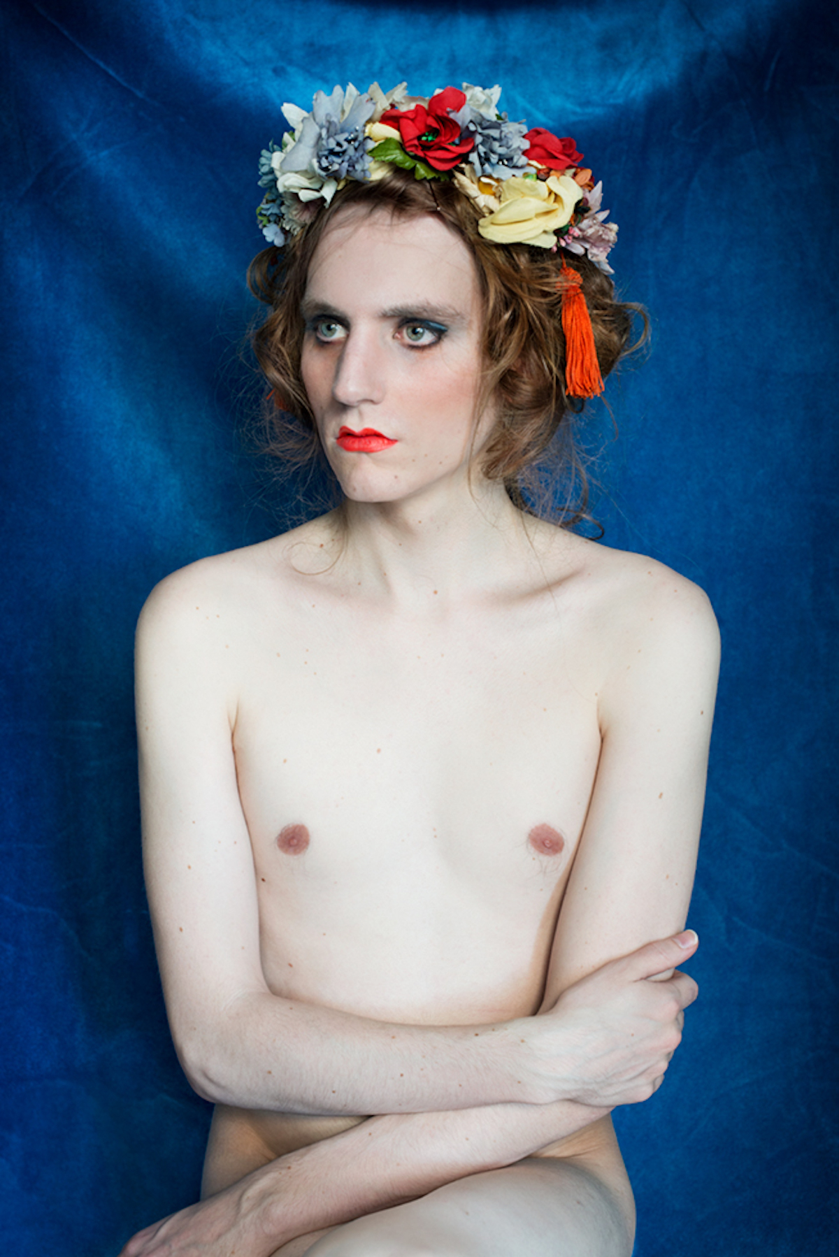 """<p """"="""""""">A photograph of a person sitting with legs and arms crossed and wearing a floral headband."""
