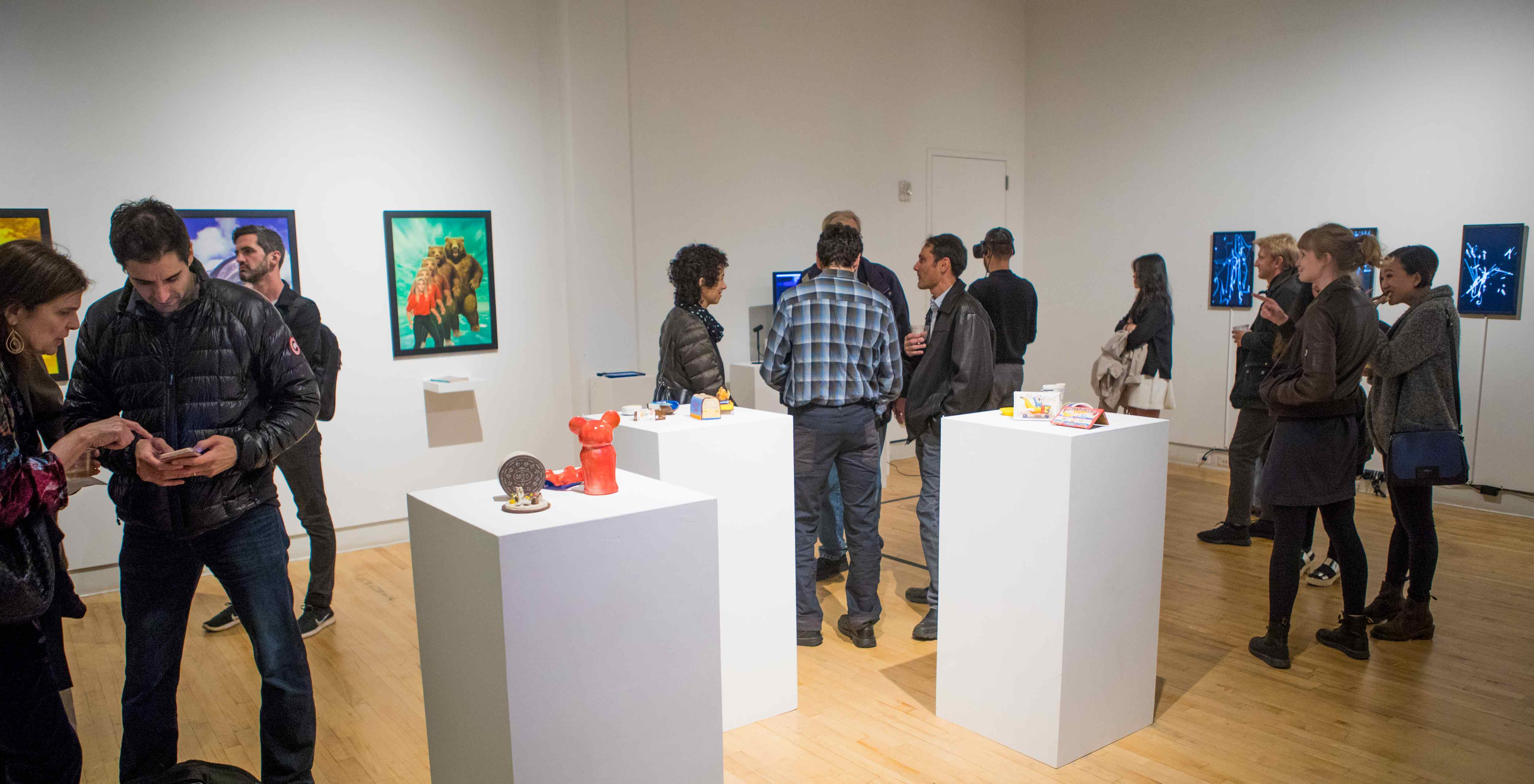 A group of people visiting with each other in an art gallery.