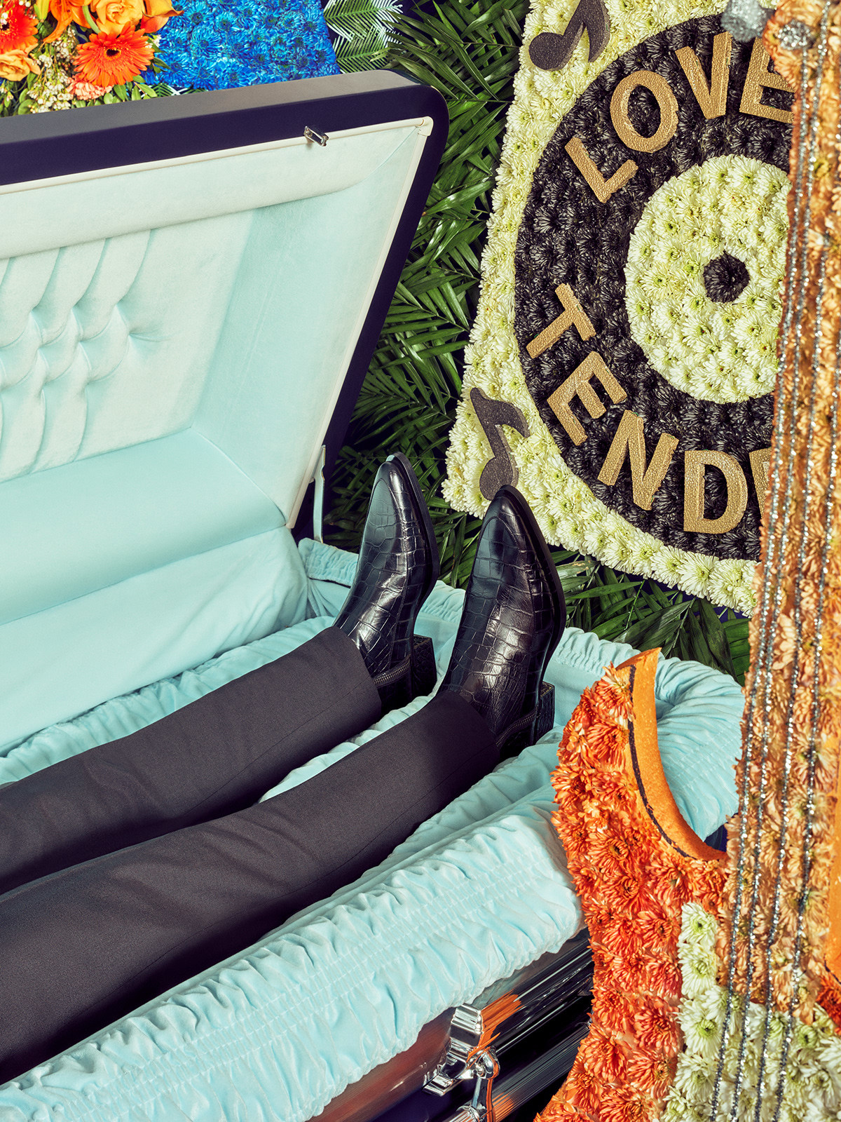 """<p """"="""""""">A photograph of the lower half of an open casket, showing the decedent's legs and boots. The casket is surrounded by colorful floral arrangements, including one shaped to look like an electric bass guitar."""