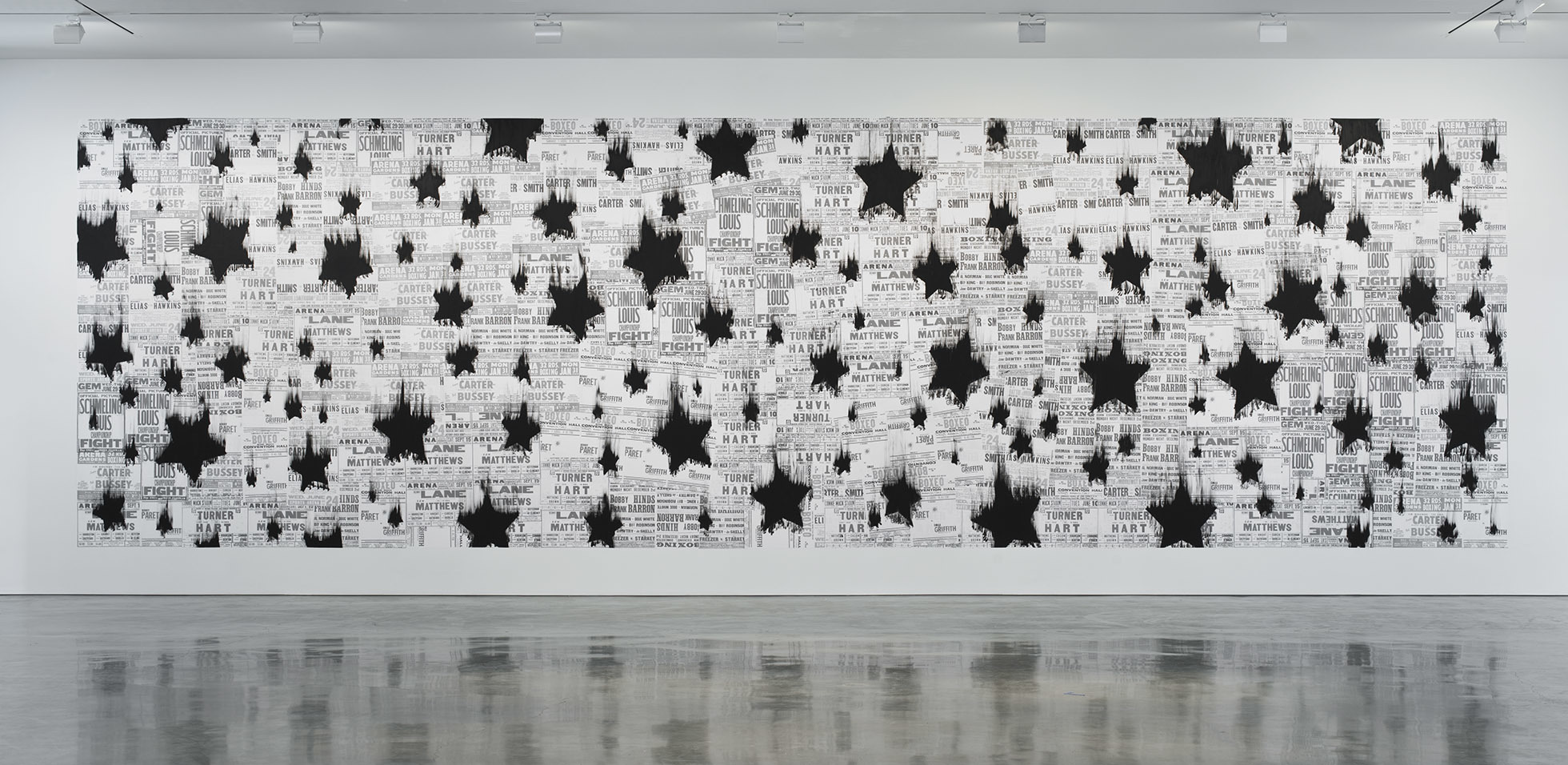 """<p """"="""""""">A large monochrome mural consisting of black stars painted over a collage of boxing-poster reproductions."""