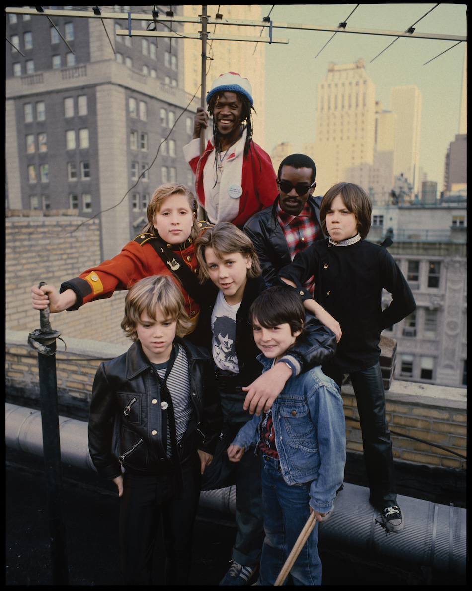 """<p """"="""""""">A color photograph of two men and five kids posing on a New York City rooftop."""