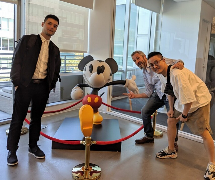 """<p """"="""""""">Three people pose for a photograph in front of a roped-off Mickey Mouse statue."""