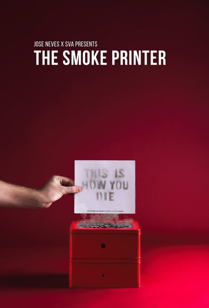 "An ad design for ""The Smoke Printer"" with a hand holding a piece of paper on top of a smoking printer."