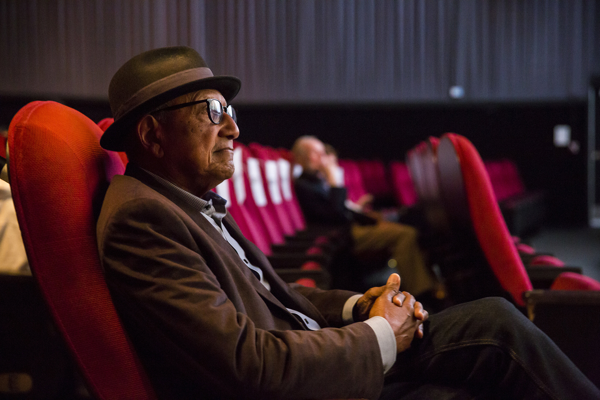 man in shit with hat and glasses i the cinema