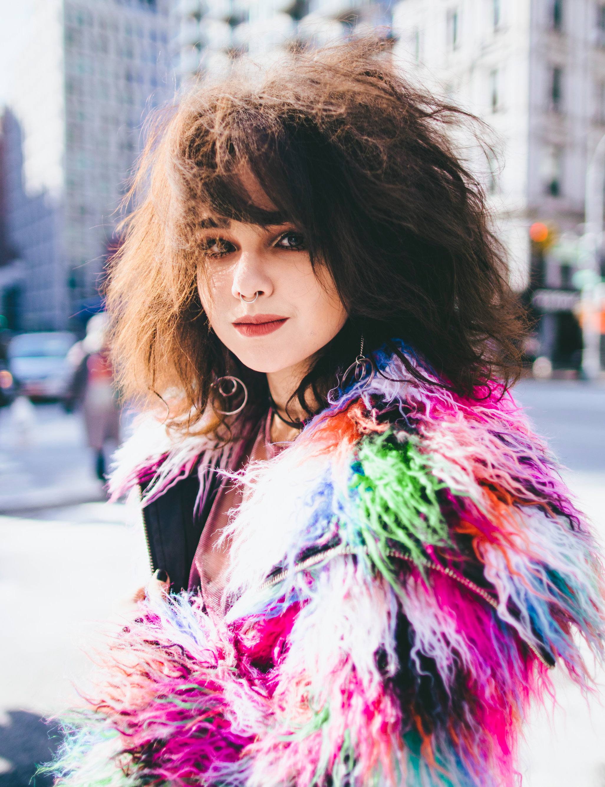 """<p """"="""""""">A young woman in a multicolored coat on a New York City street."""