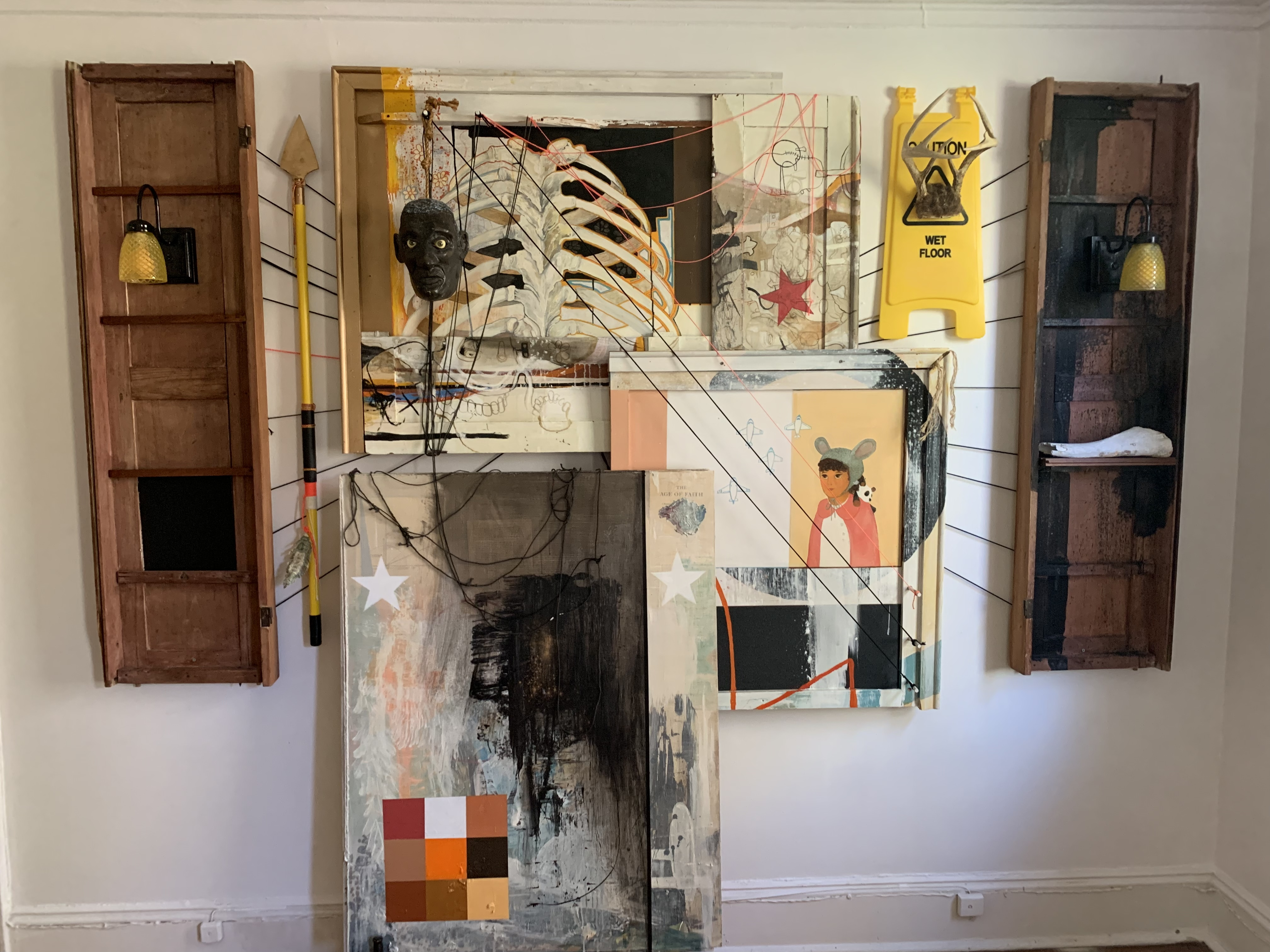 """<p """"="""""""">a mixed media installation on a white wall. it features paintings, wooden panels, and more"""